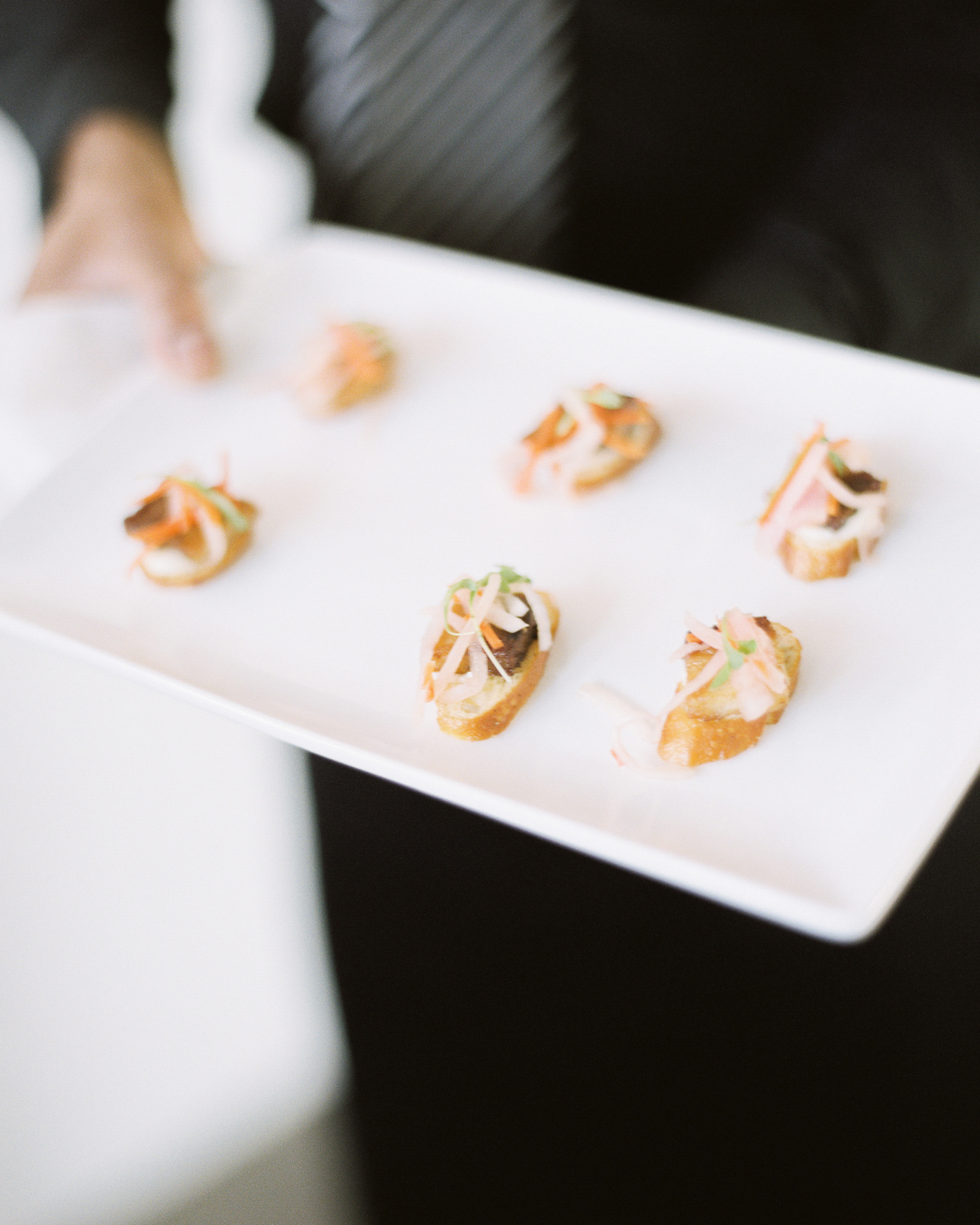 man holding rectangle plate of wedding appetizers