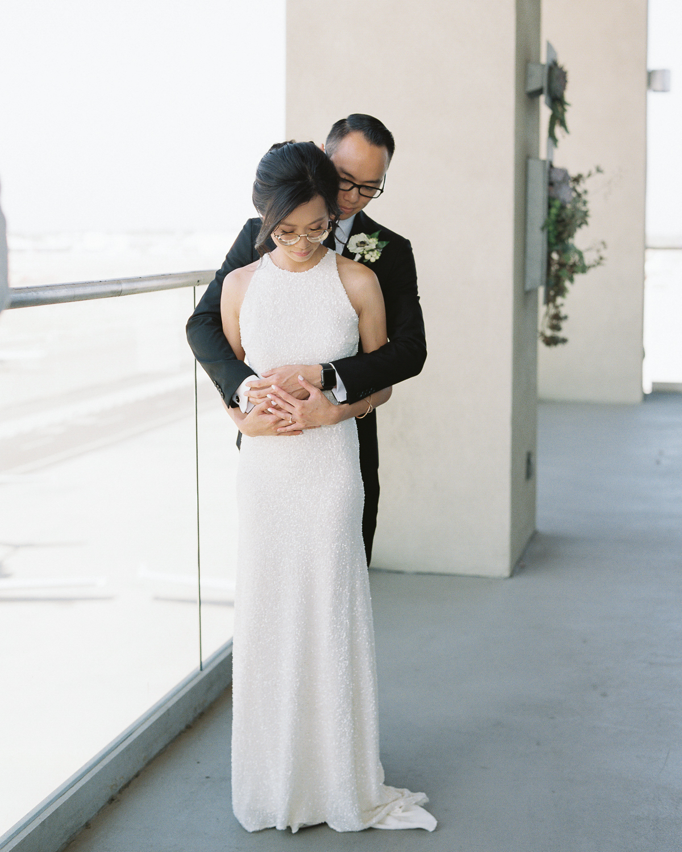 wedding groom holding bride near large window