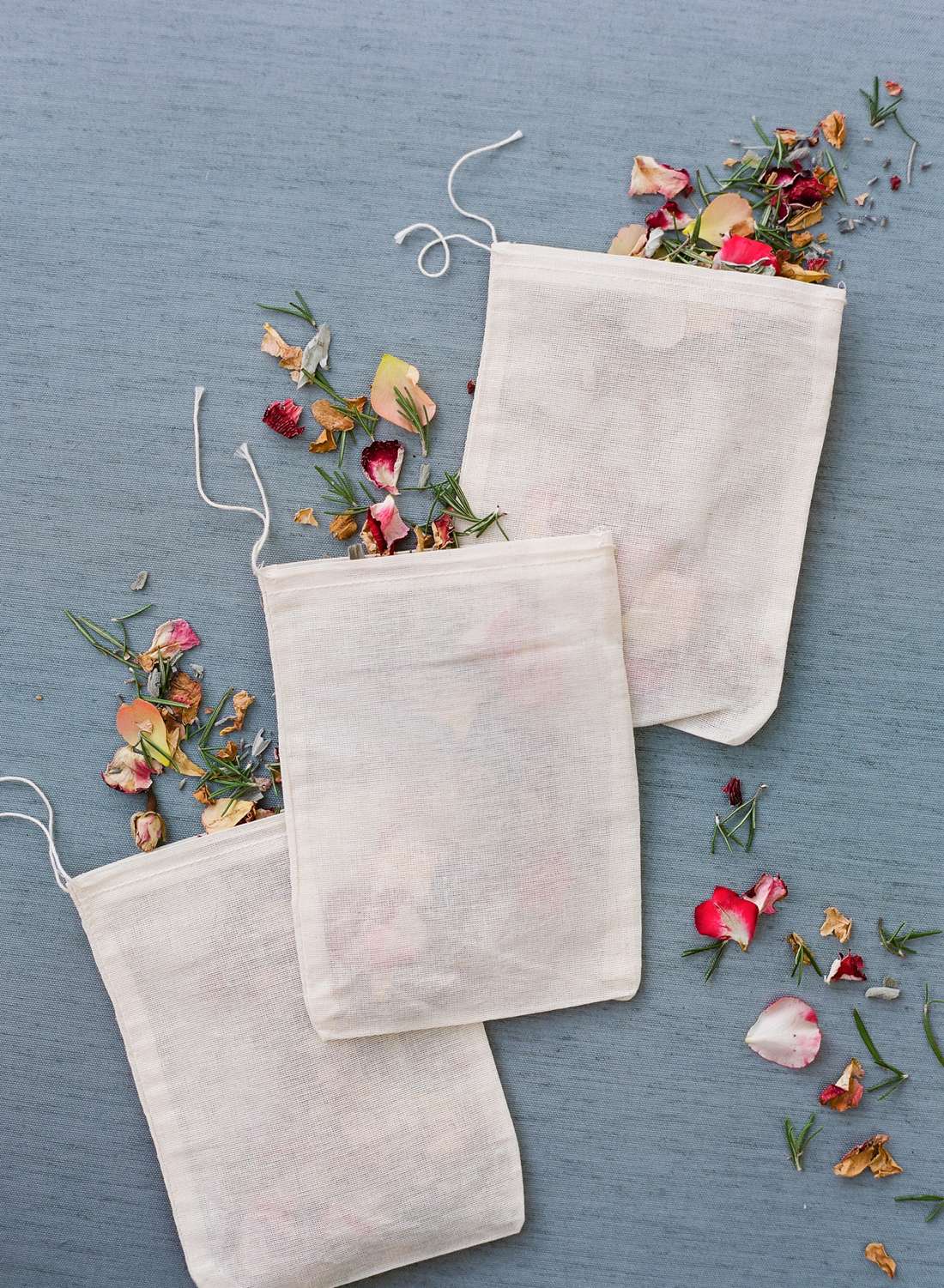 white pouches filled with dried flower petals and herbs