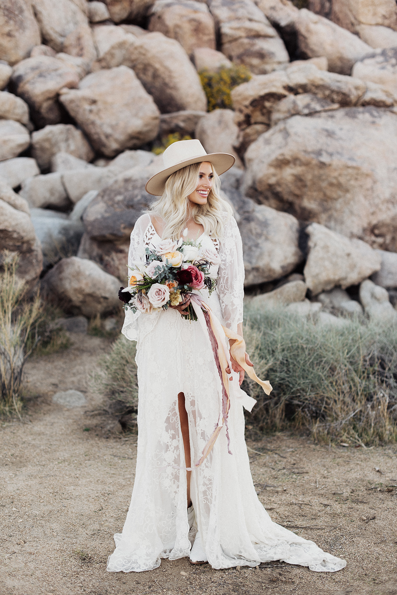 bride wearing hat and lace gown in desert