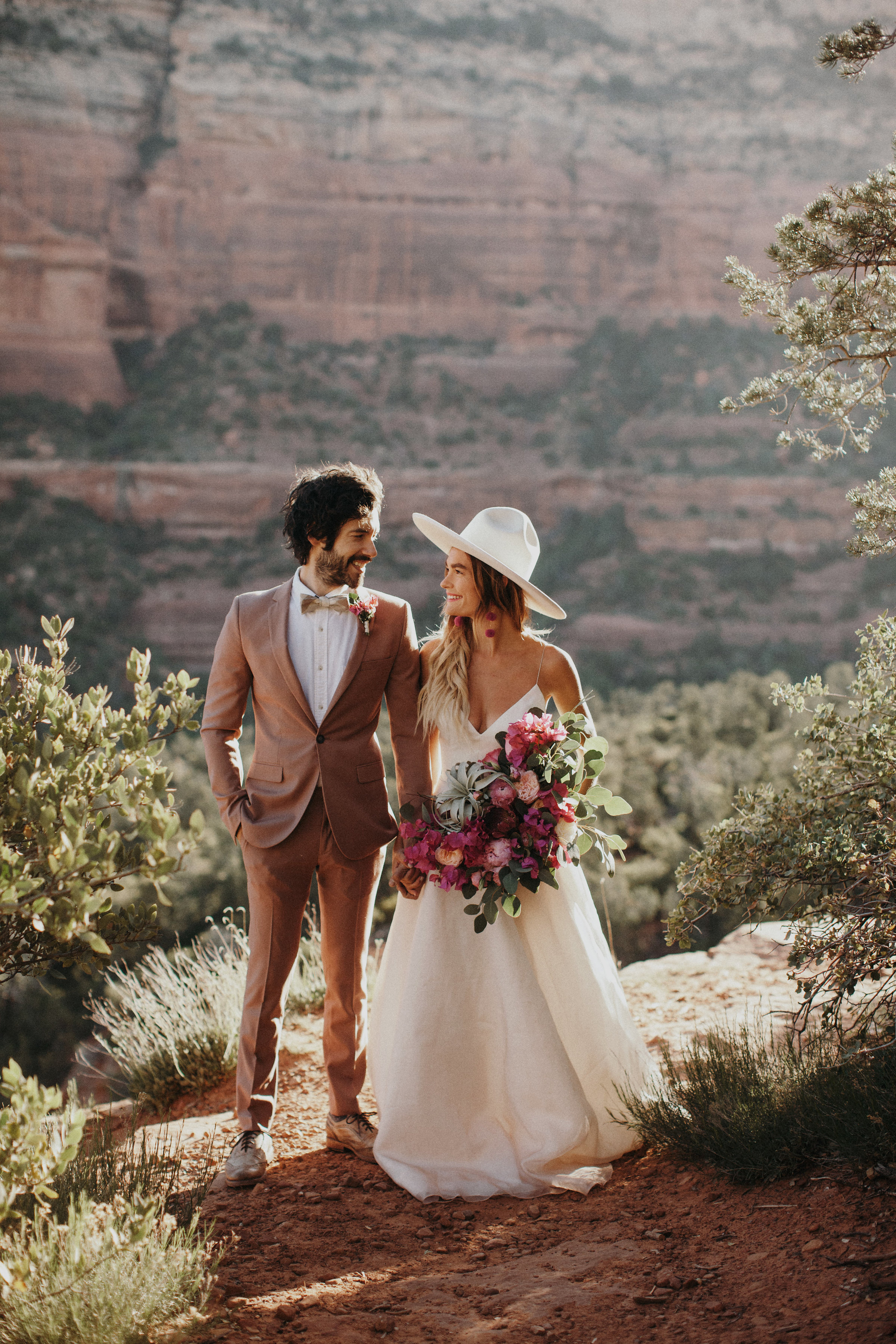bride wearing white hat and gown in desert