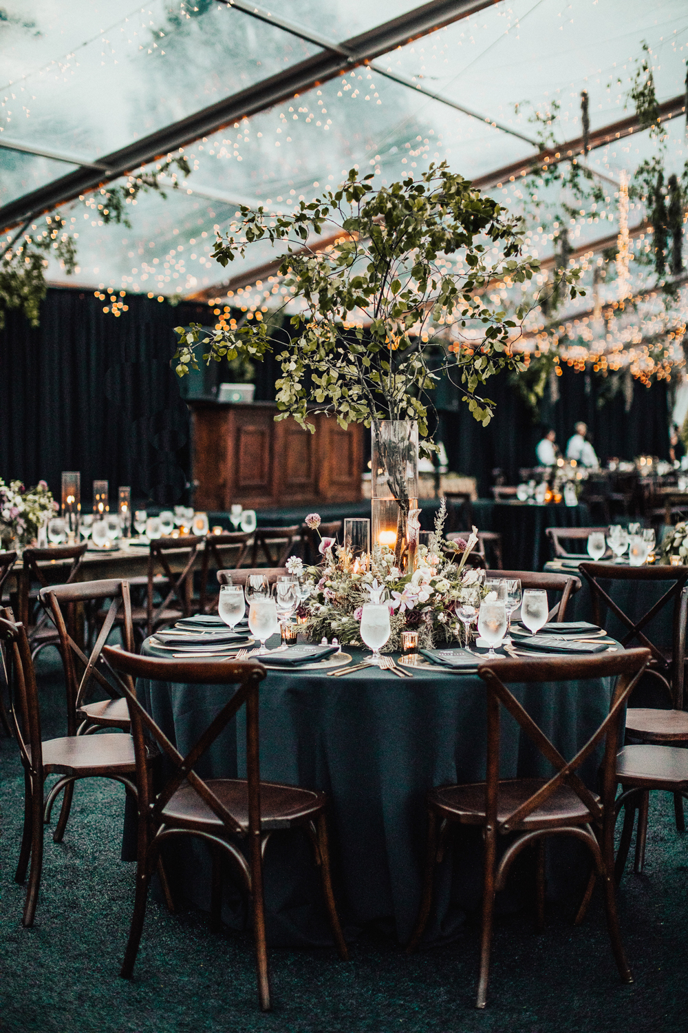 round tables with dark green linens inside glass tent reception