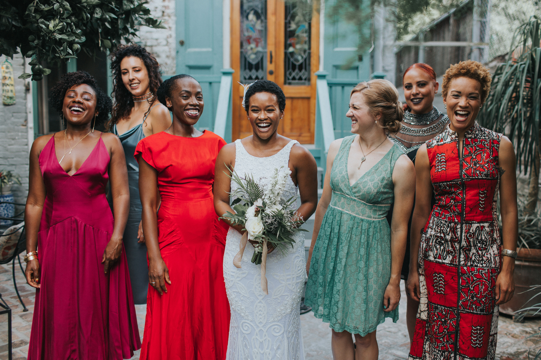 bride with women in mismatched red and green dresses