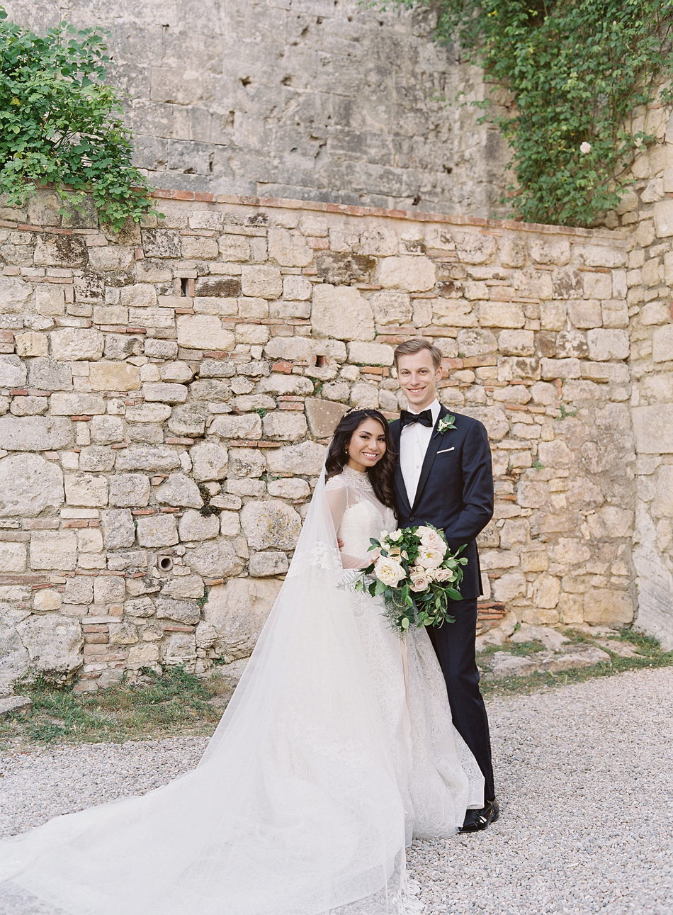 bride and groom pose in front of stone wall