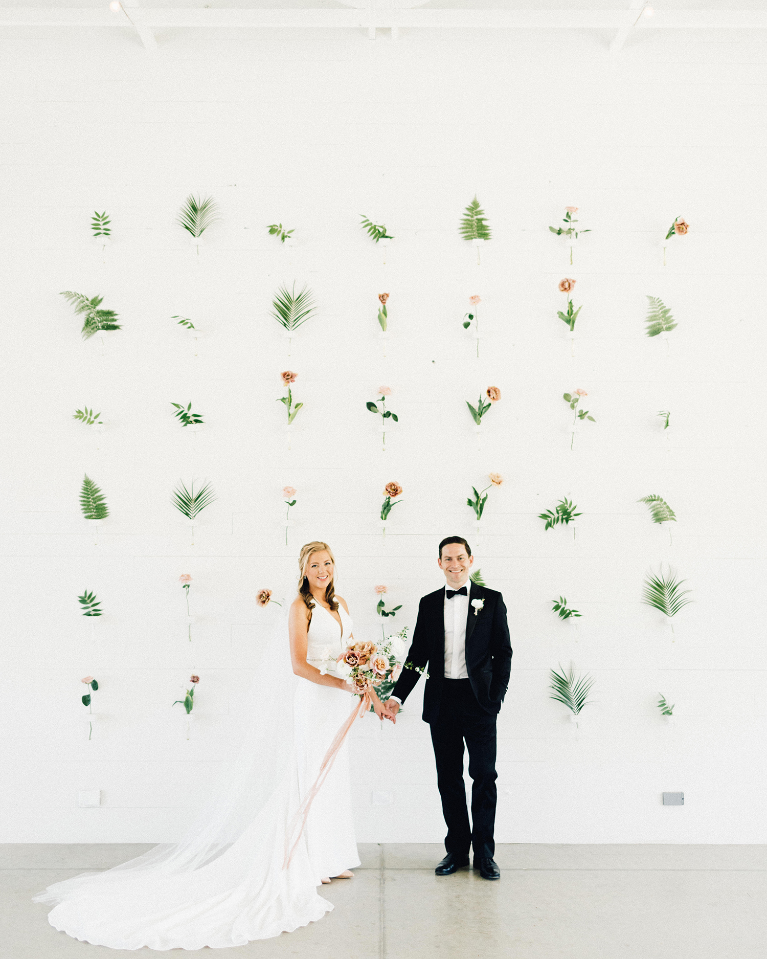 amanda chuck wedding couple in front of white wall with hanging flowers