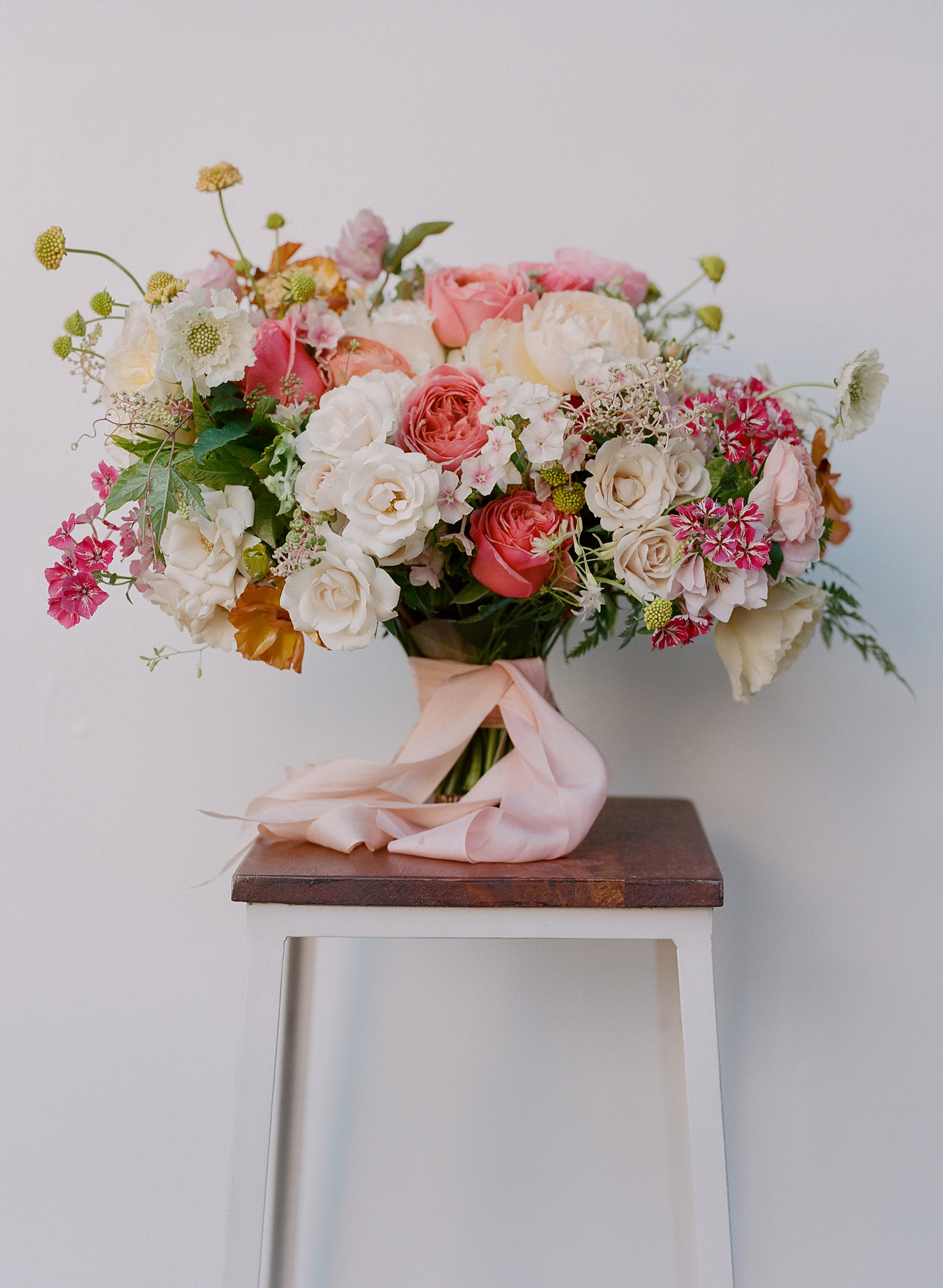 bouquet of white and pink roses with ranunculus and poke weed