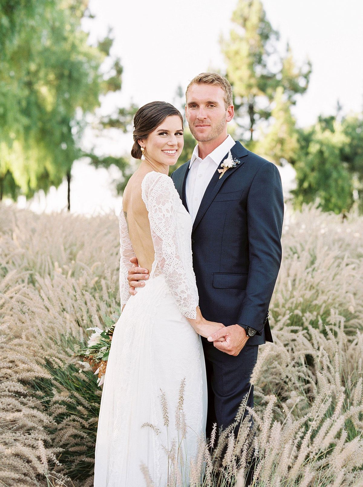 jena donny wedding couple holding hands in tall grass