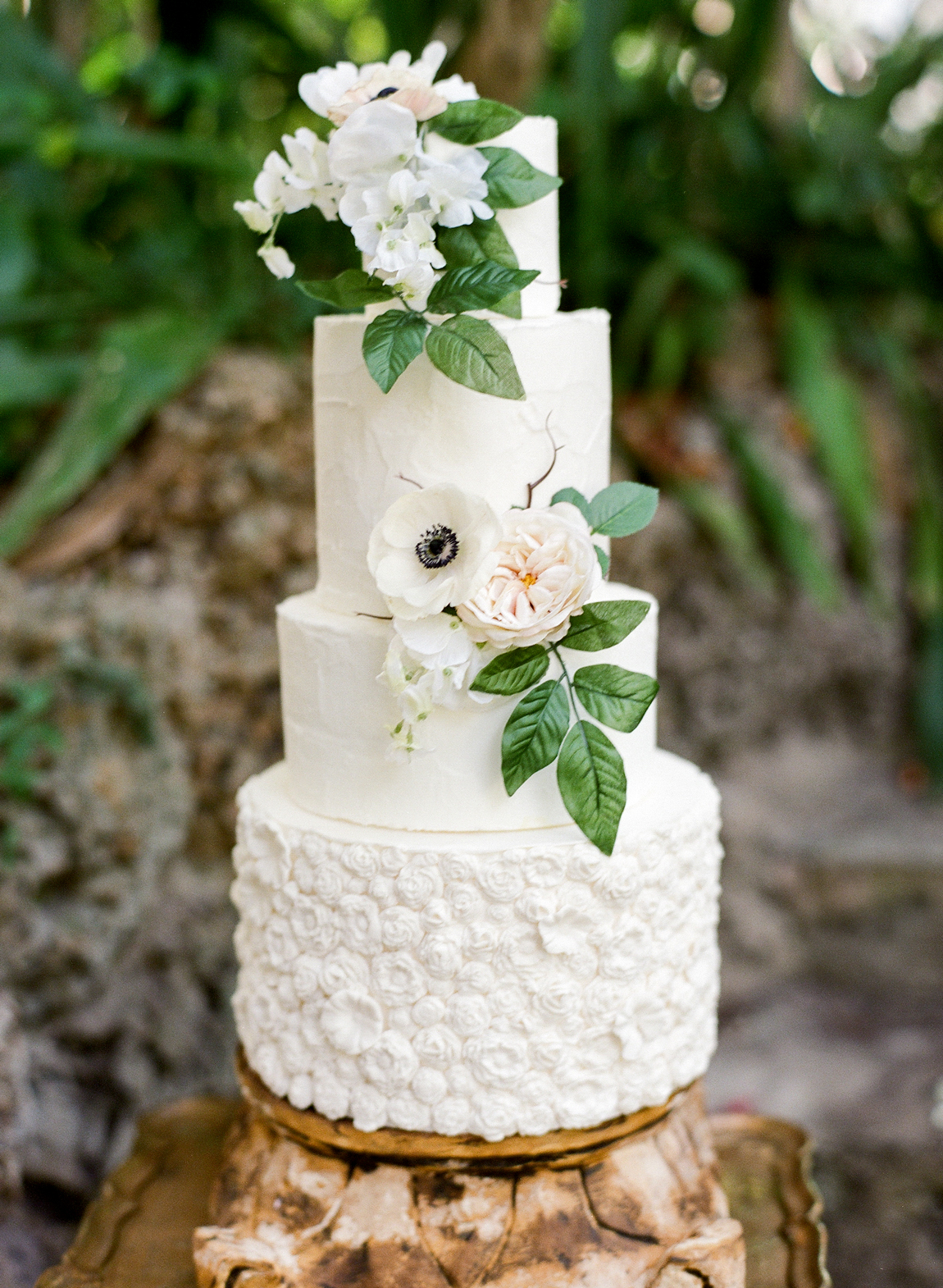 four tiered white frosted bas-relief wedding cake with floral accents