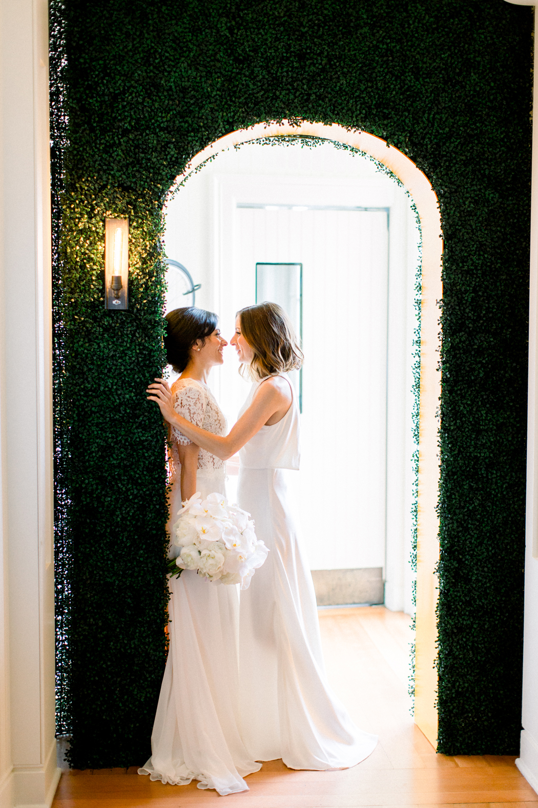 brides face each other under greenery covered doorway