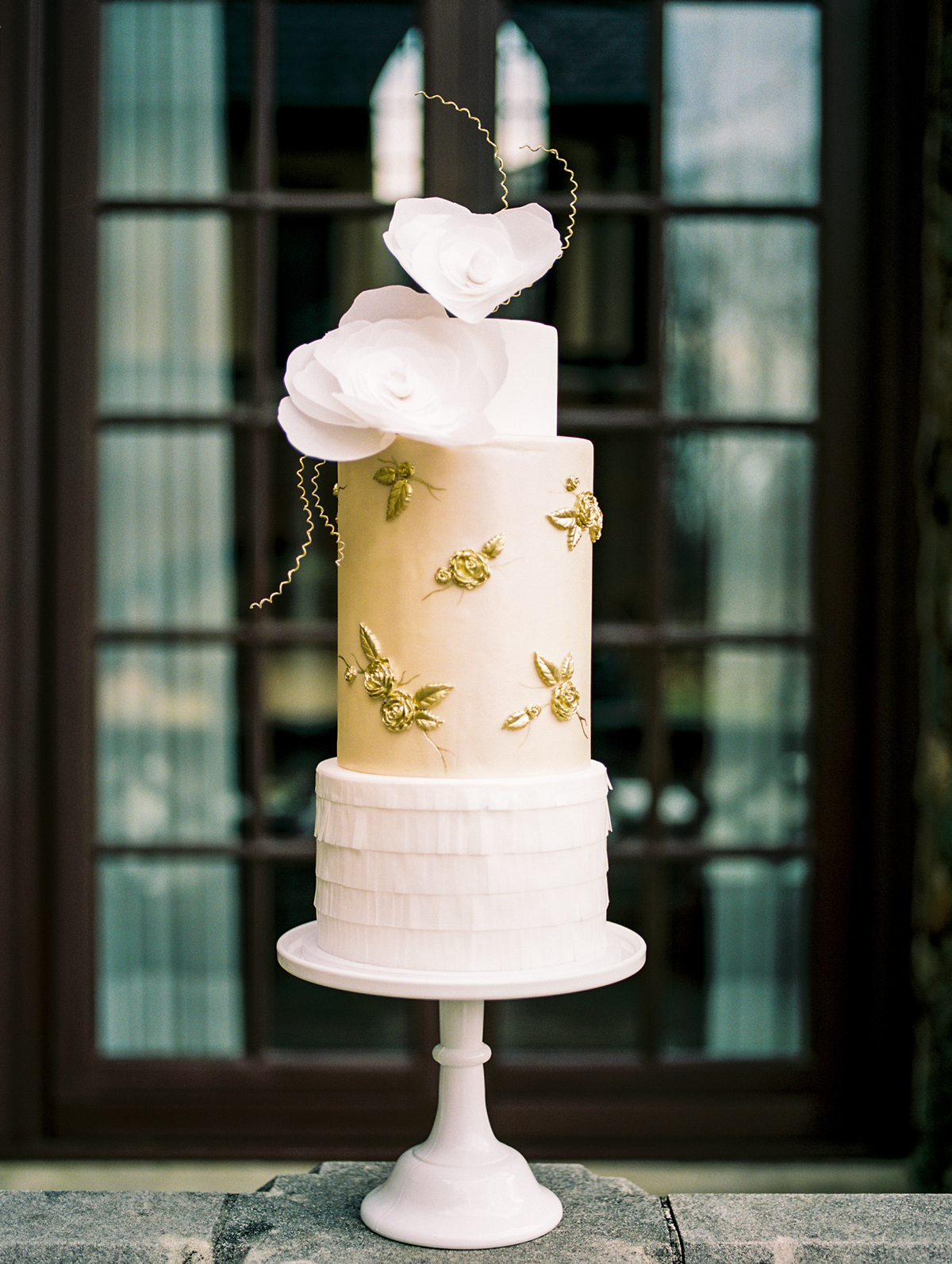 three tiered white and gold frosted bas-relief wedding cake