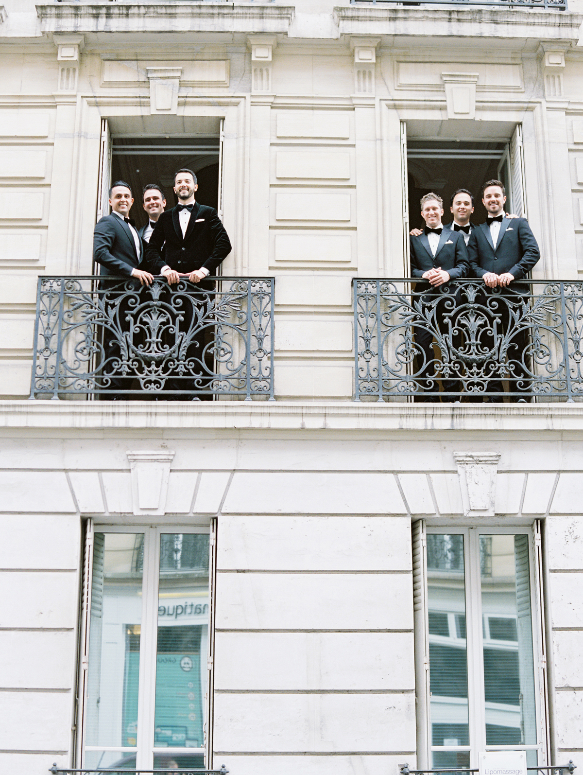 groom and groomsmen posing at window balcony of parisian building