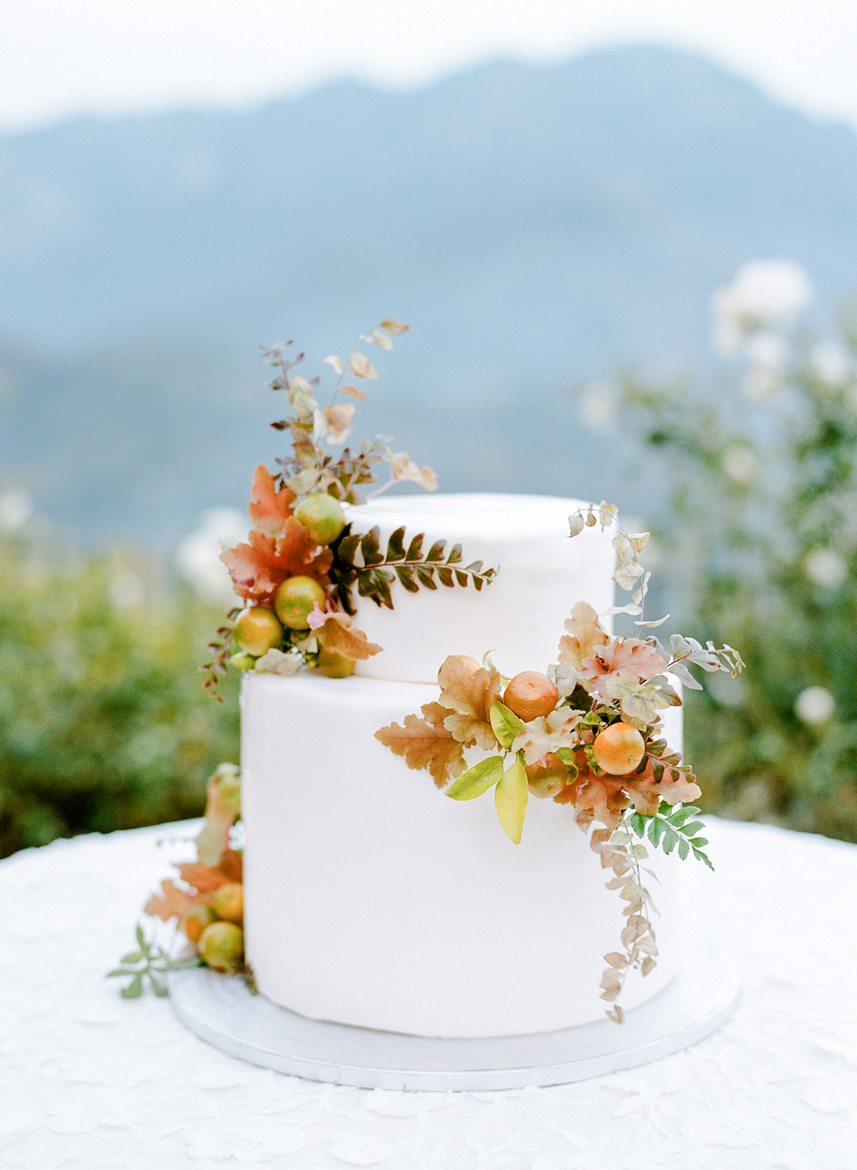 two tiered white frosted wedding cake with fall floral and citrus accents