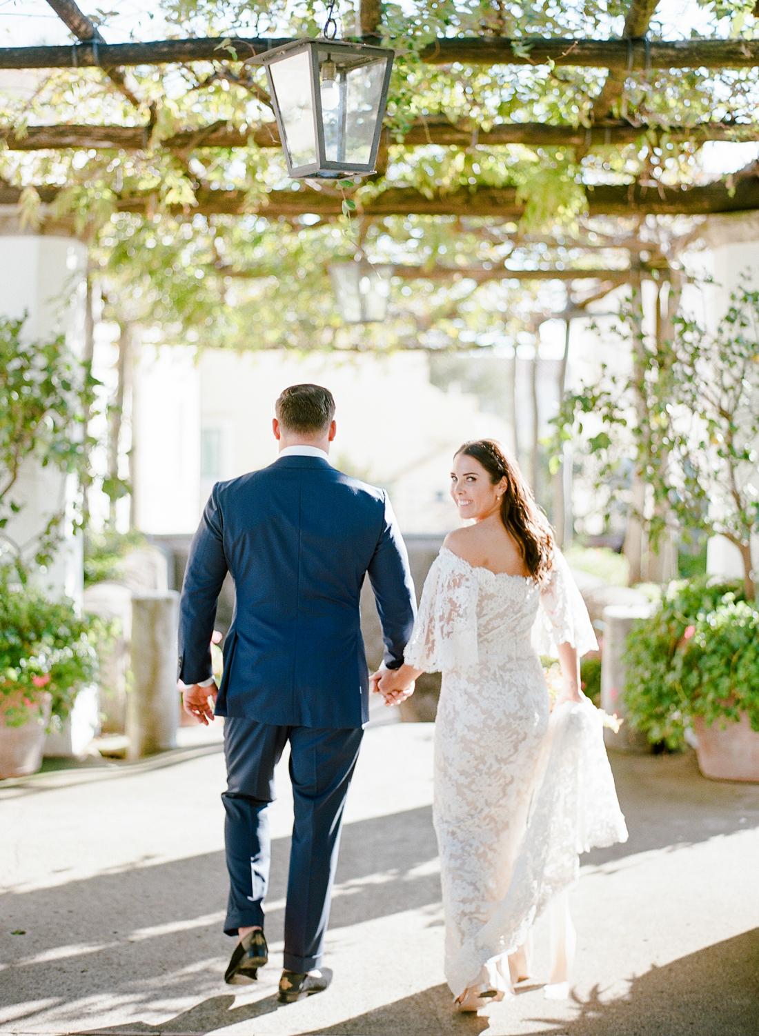 bride and groom walk away in garden terrace area