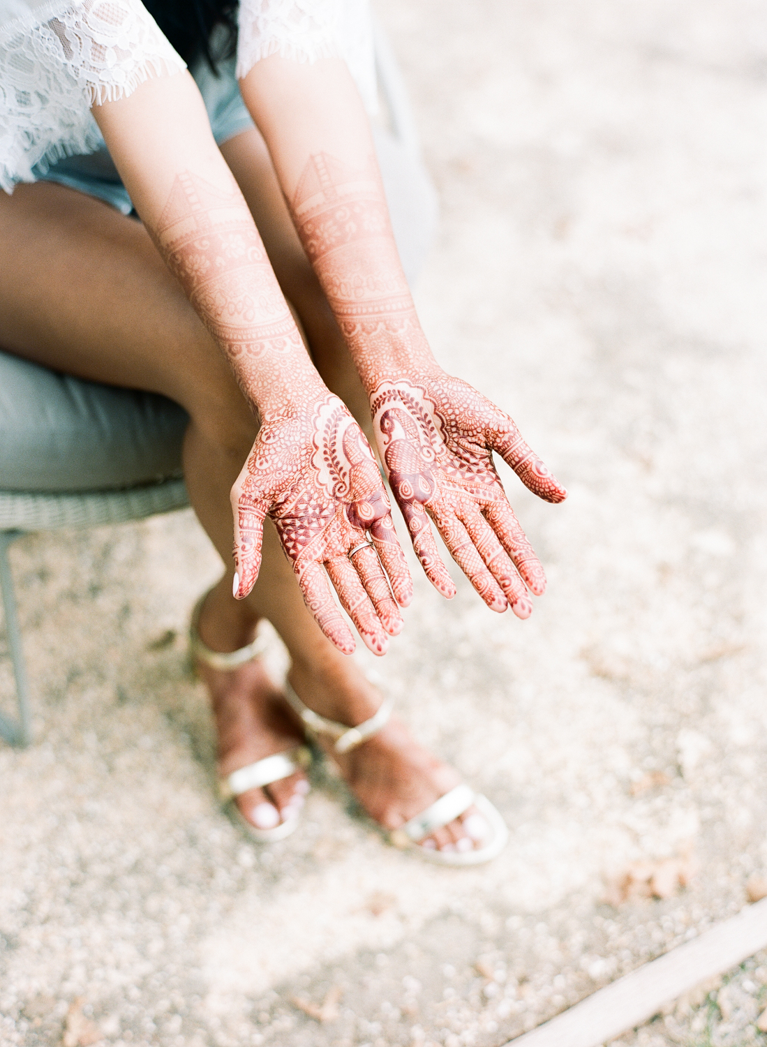 bride wearing henna design on hands and forearms