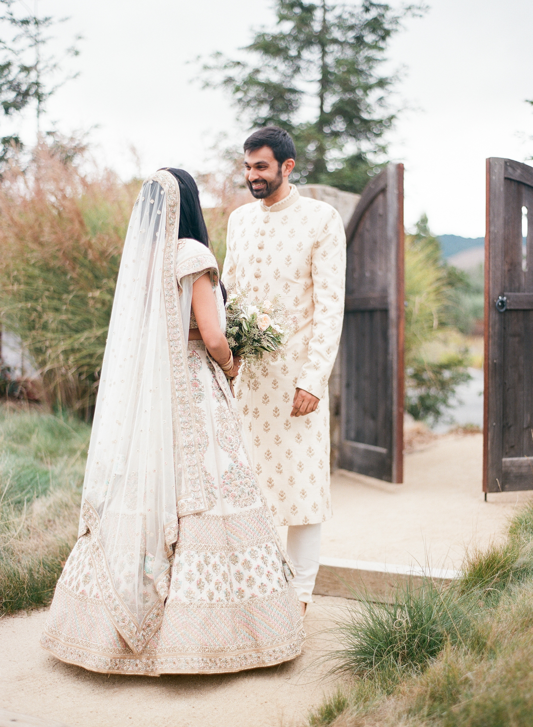 bride and groom share first look in garden area before wedding ceremony