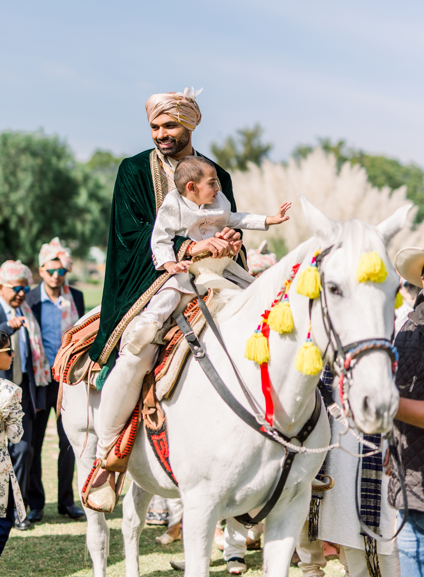 groom arriving to the wedding on white horse