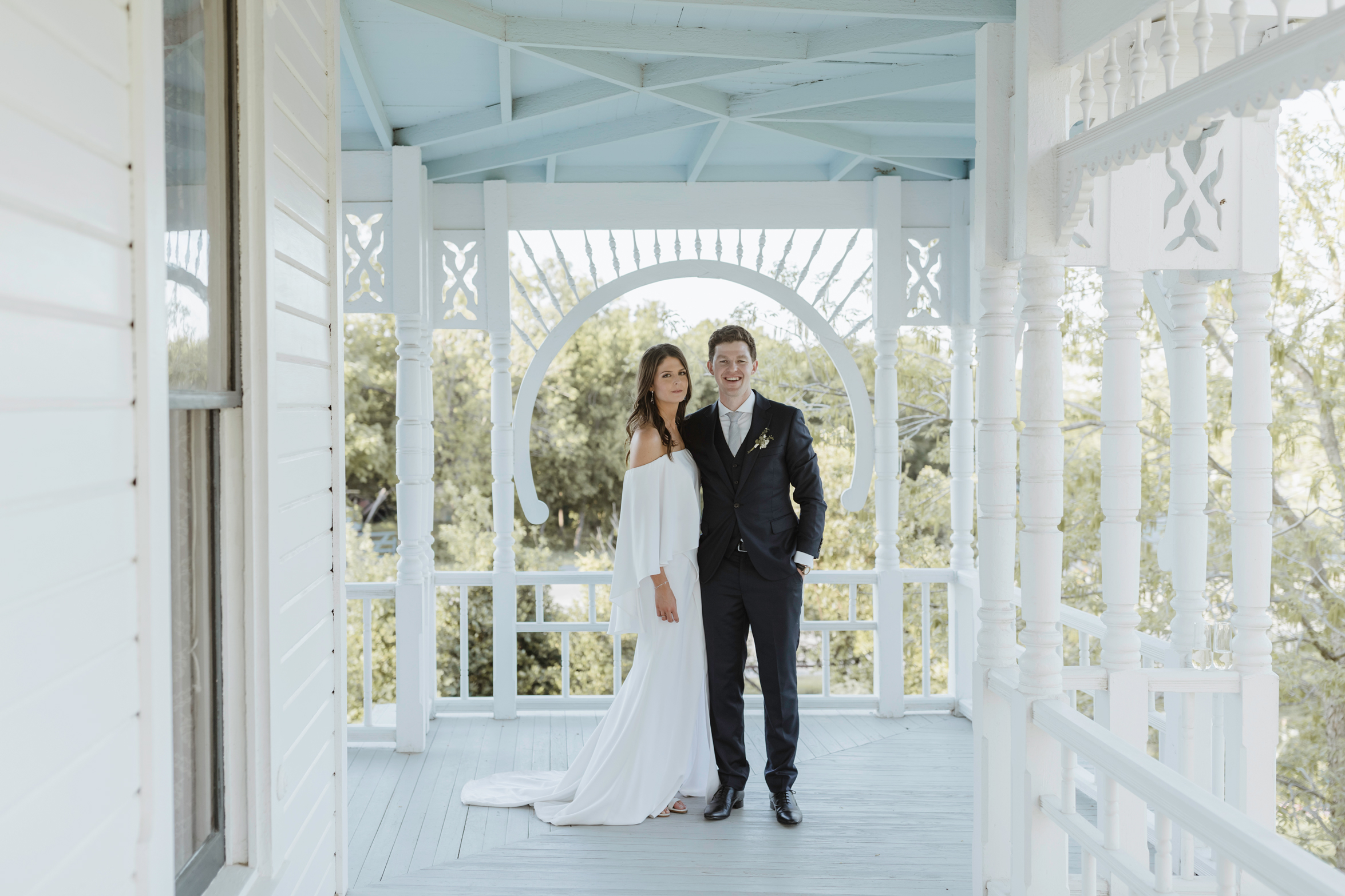 bride and groom posing on white porch outside