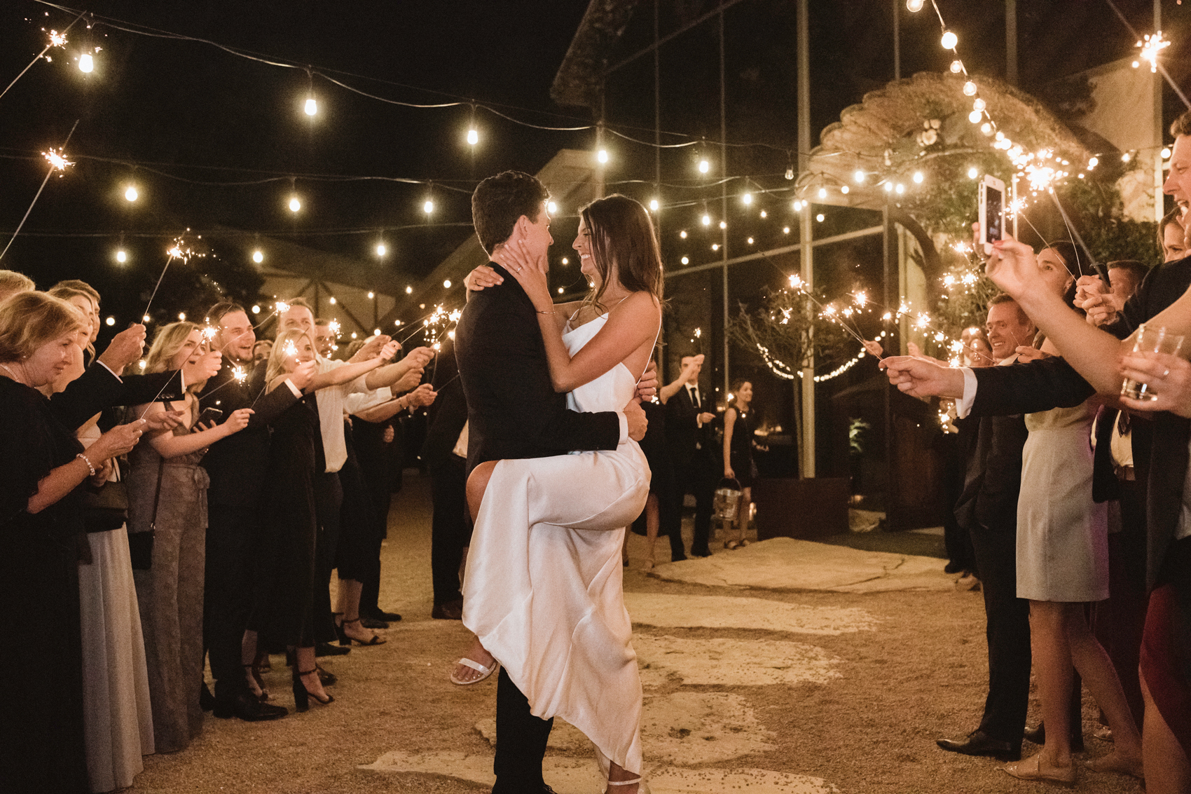 guests hold sparklers around bride and groom outside hotel