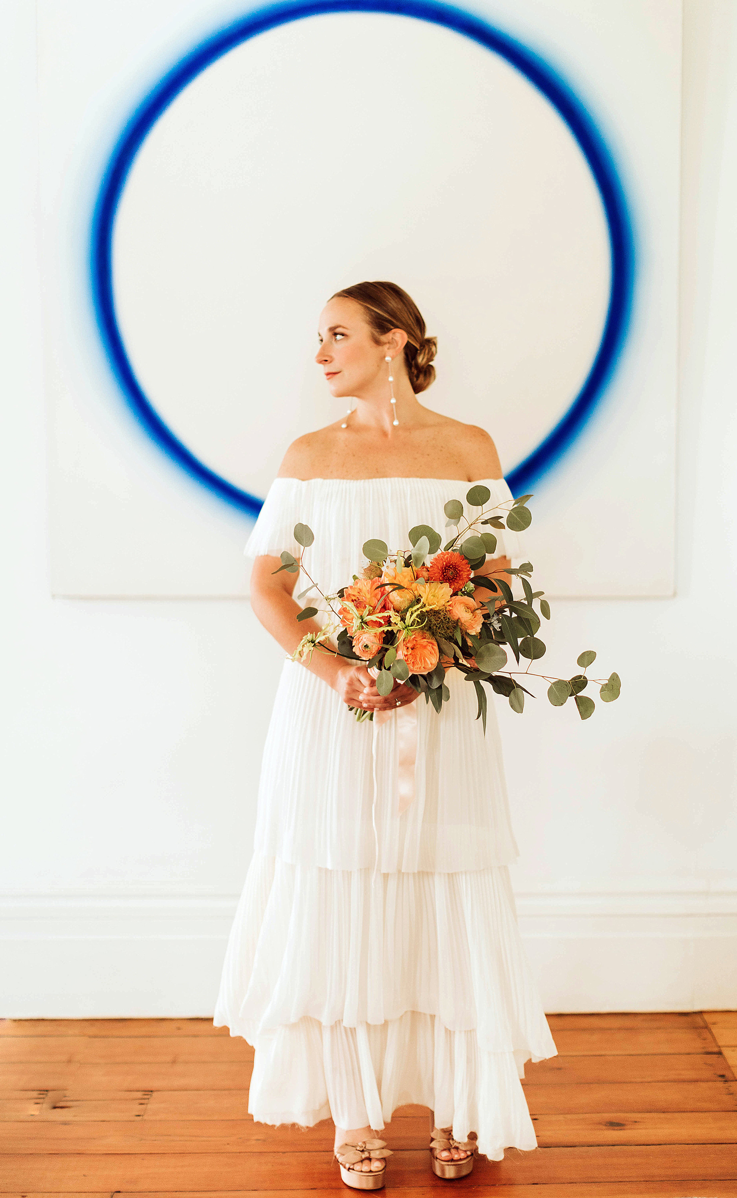 bride standing in front of contemporary blue and white painting