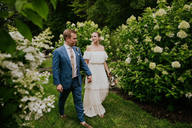 bride and groom walking through hydrangea bushes