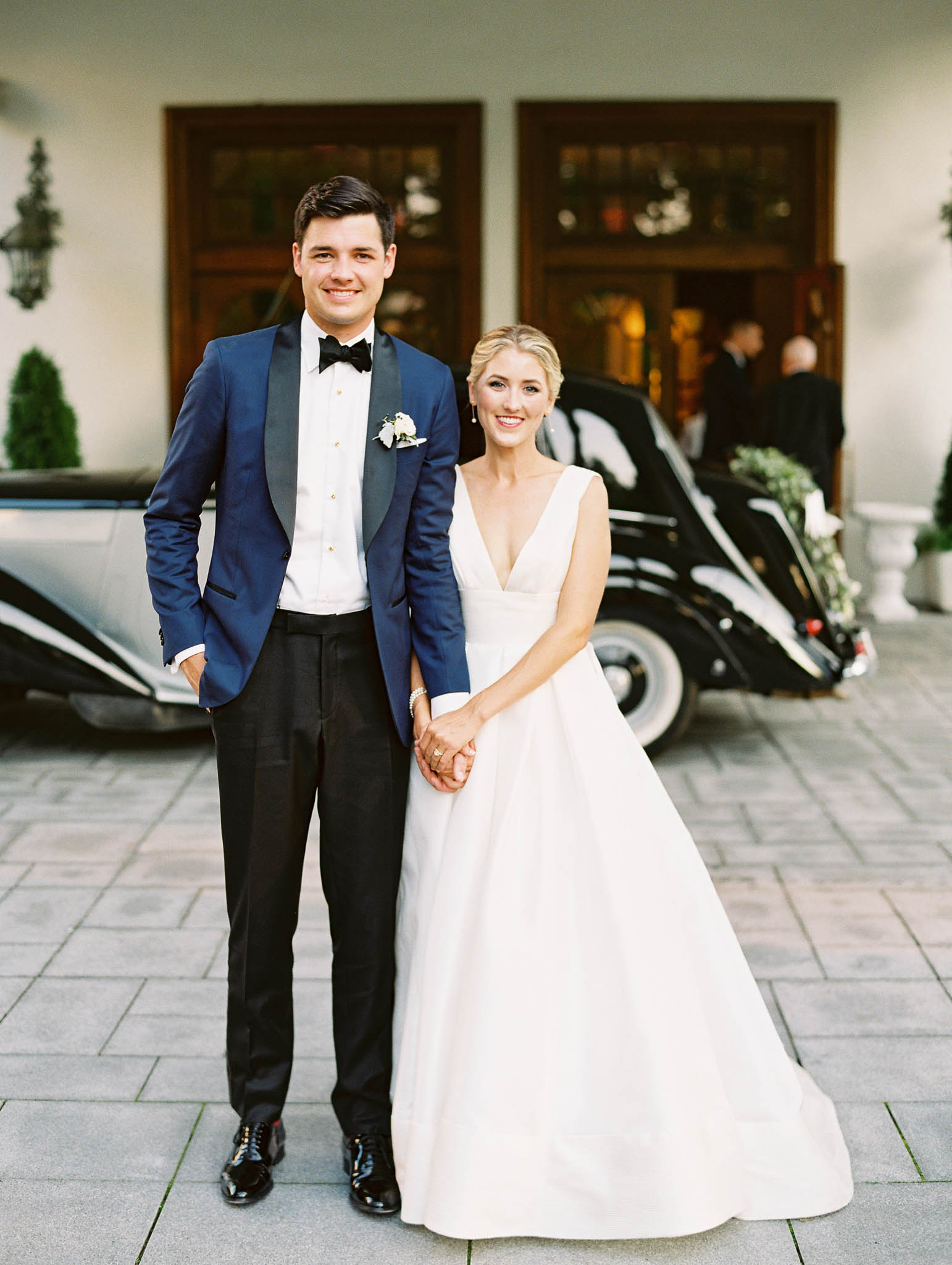 bride and groom standing outside next to vintage car