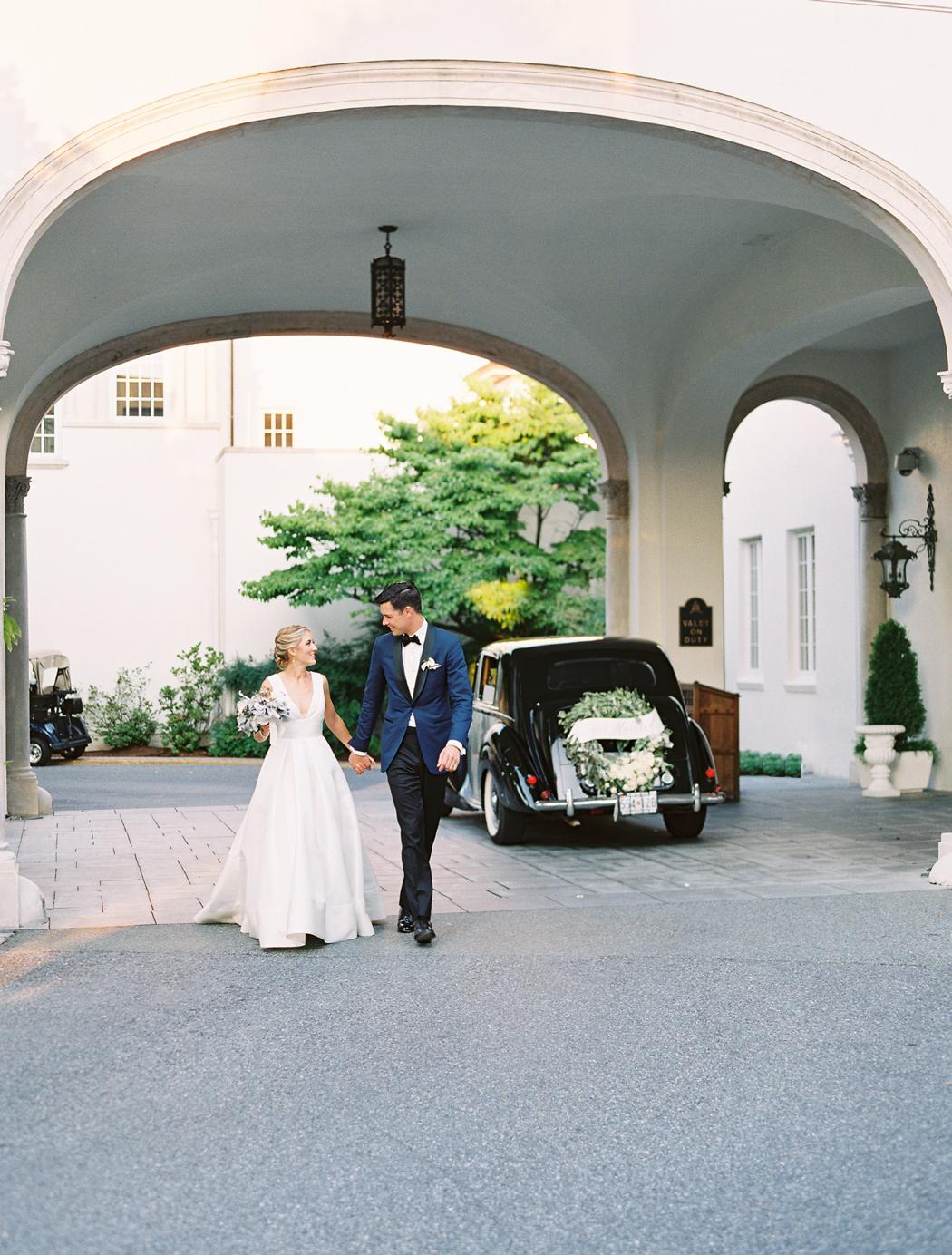 bride and groom holding hands next to black vintage car