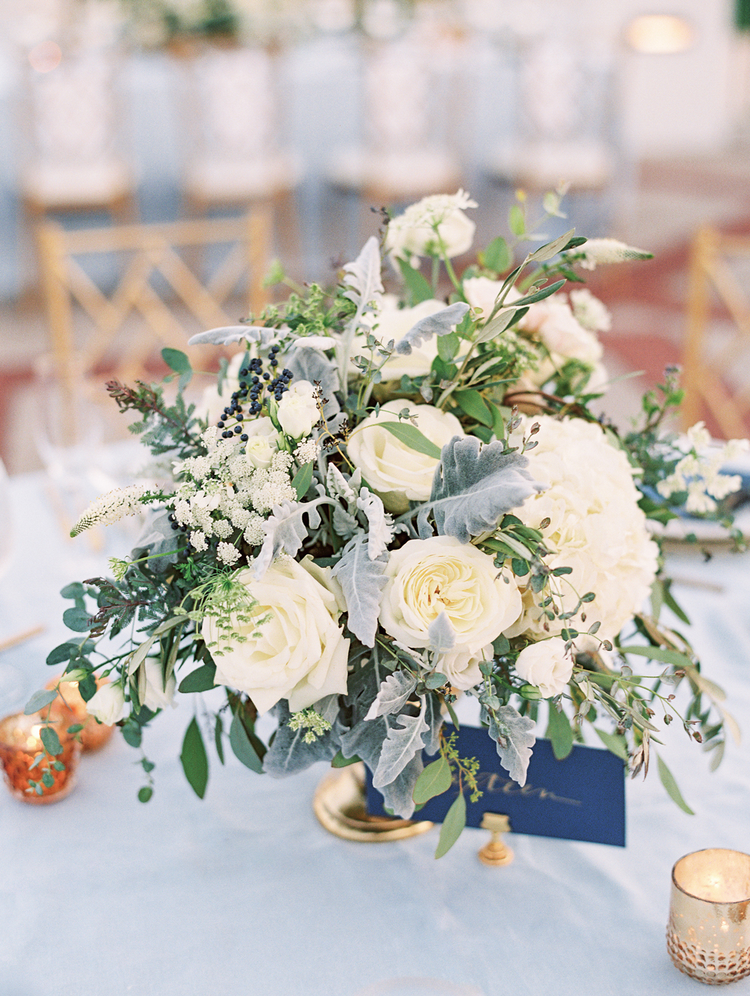 white blooms, lambs ear, and bright foliage in gold vessels centerpieces