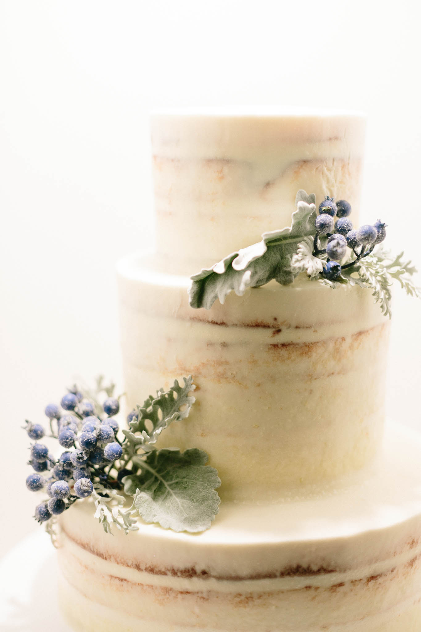 three tiered lemon frosted cake with sugar coated berry accents