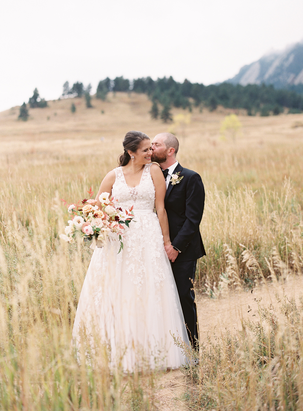 groom kisses bride on the cheek standing in the middle of an open field