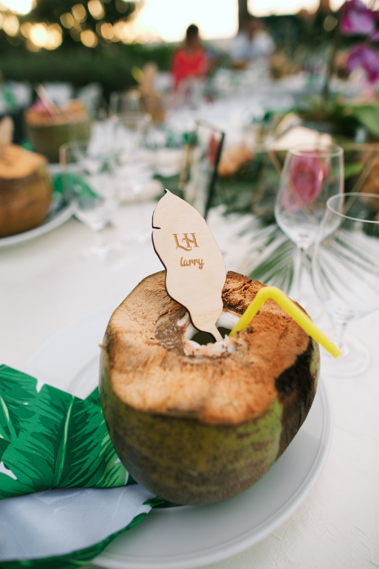 drinkable coconut with straw and wooden tropical leaf place card