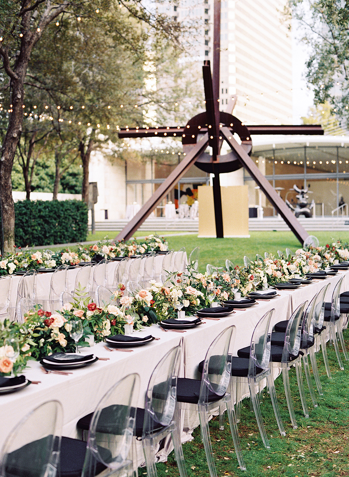 outdoor wedding reception tables near large metal sculpture