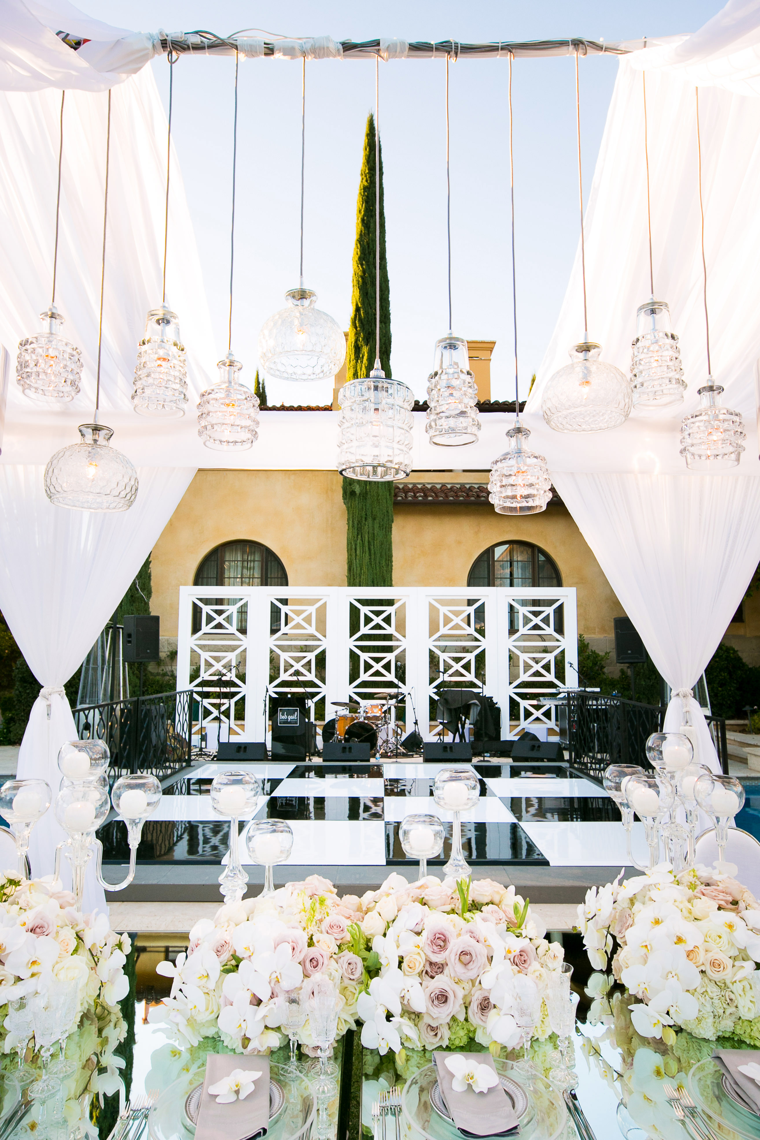 outdoor reception stage area with floral table setting and hanging lights