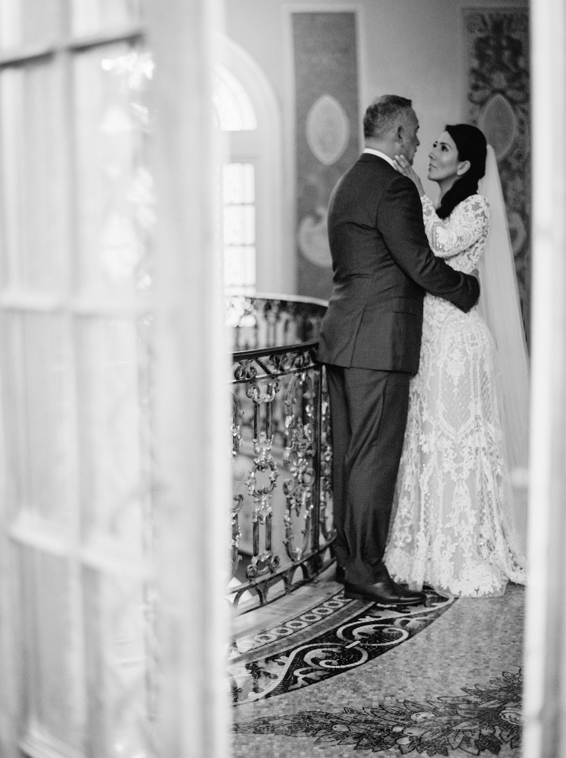 bride and groom pose inside mansion grand hallway for portrait