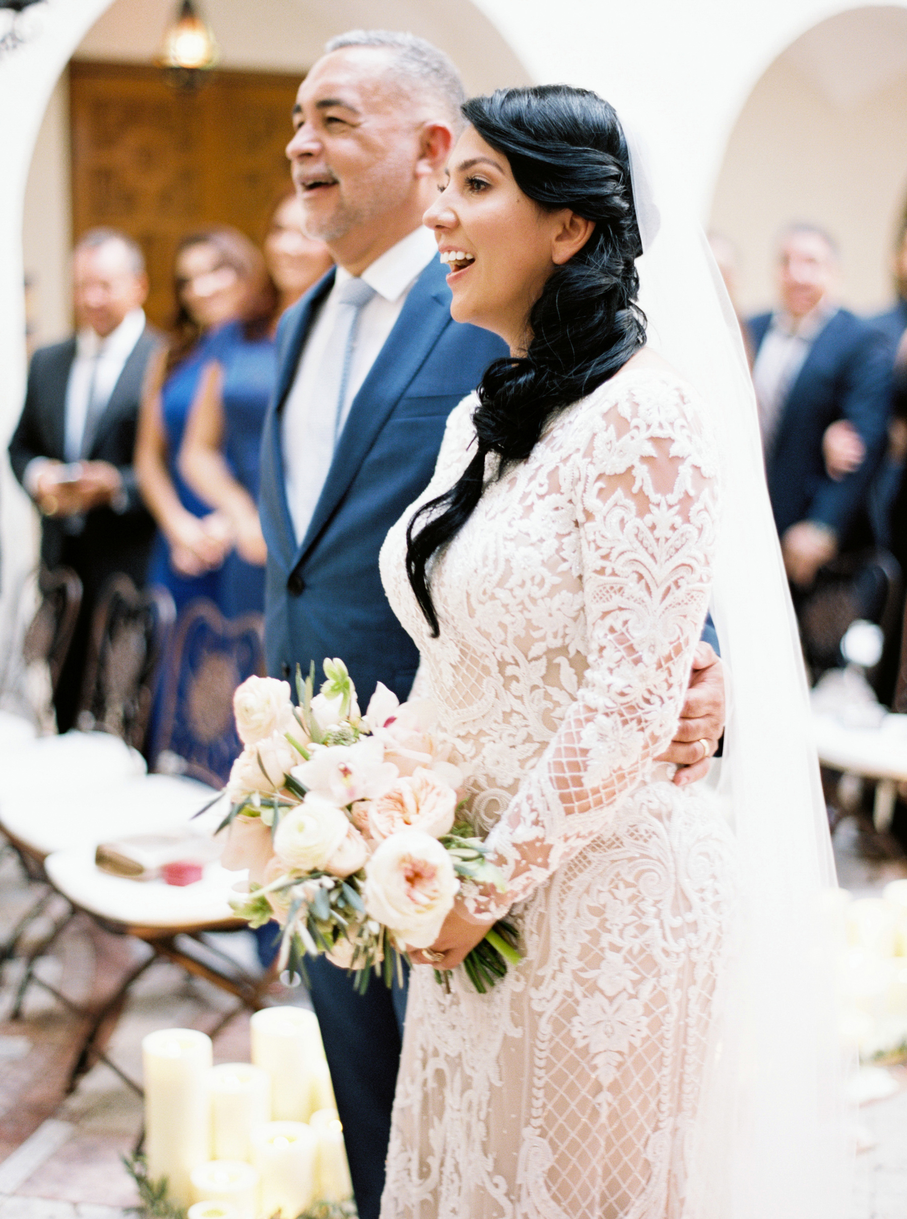 bride and groom smile during wedding ceremony vows