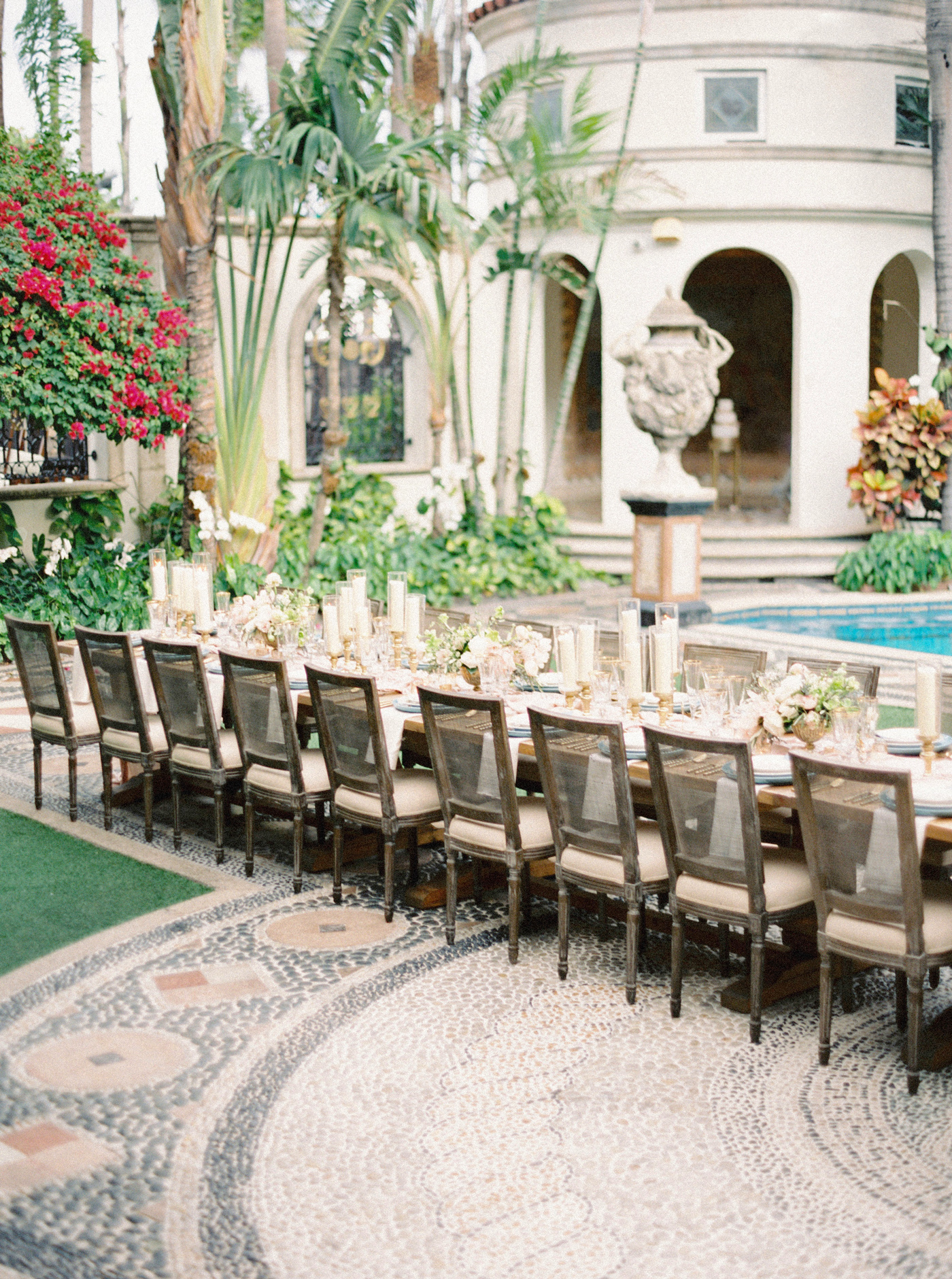 single long wedding reception table outside mansion next to pool area