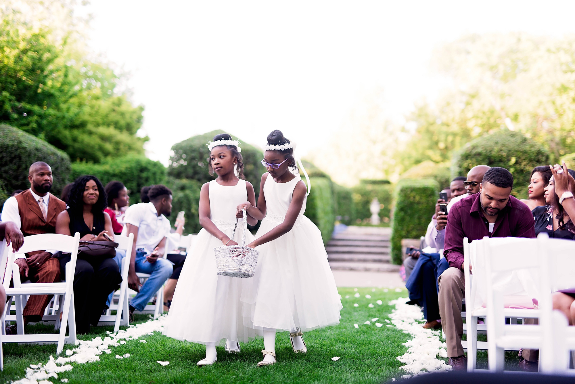 two flower girls walk down processional aisle