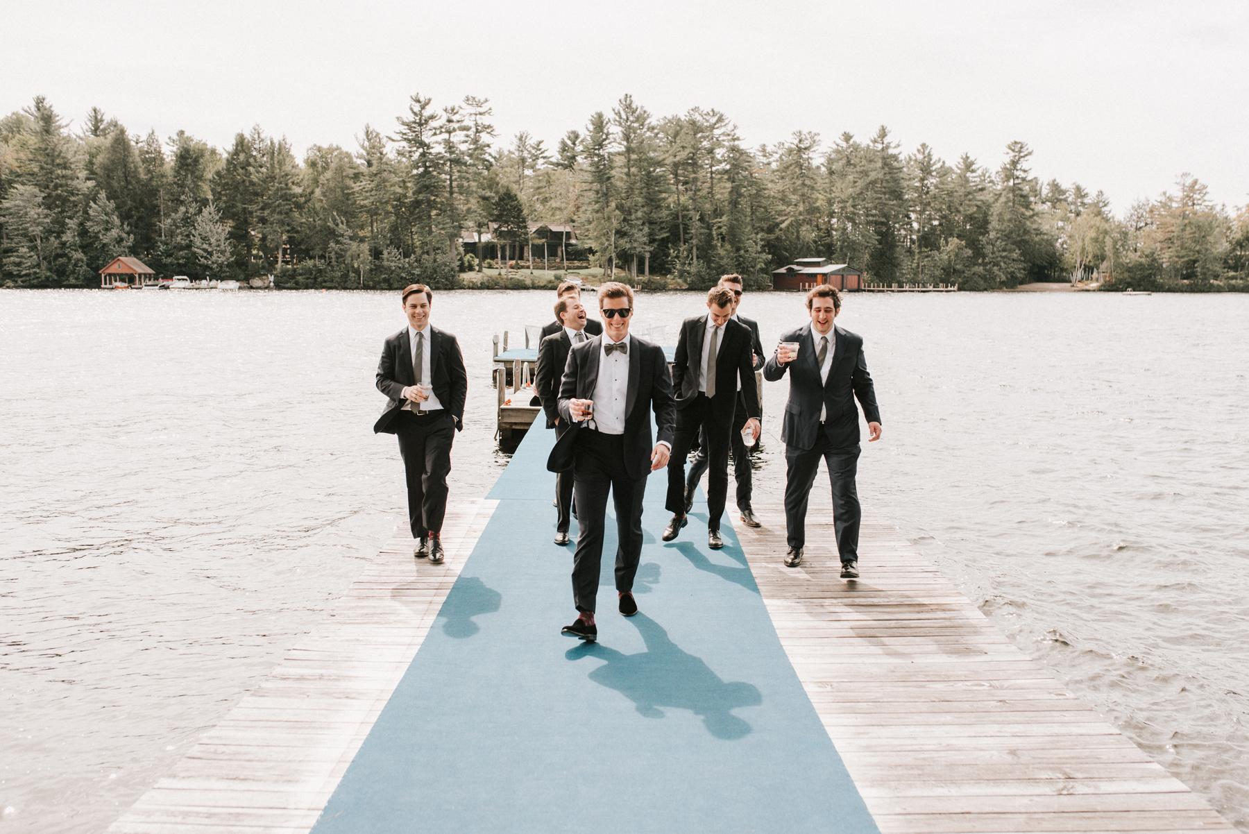 groom with groomsmen walking down lake doc