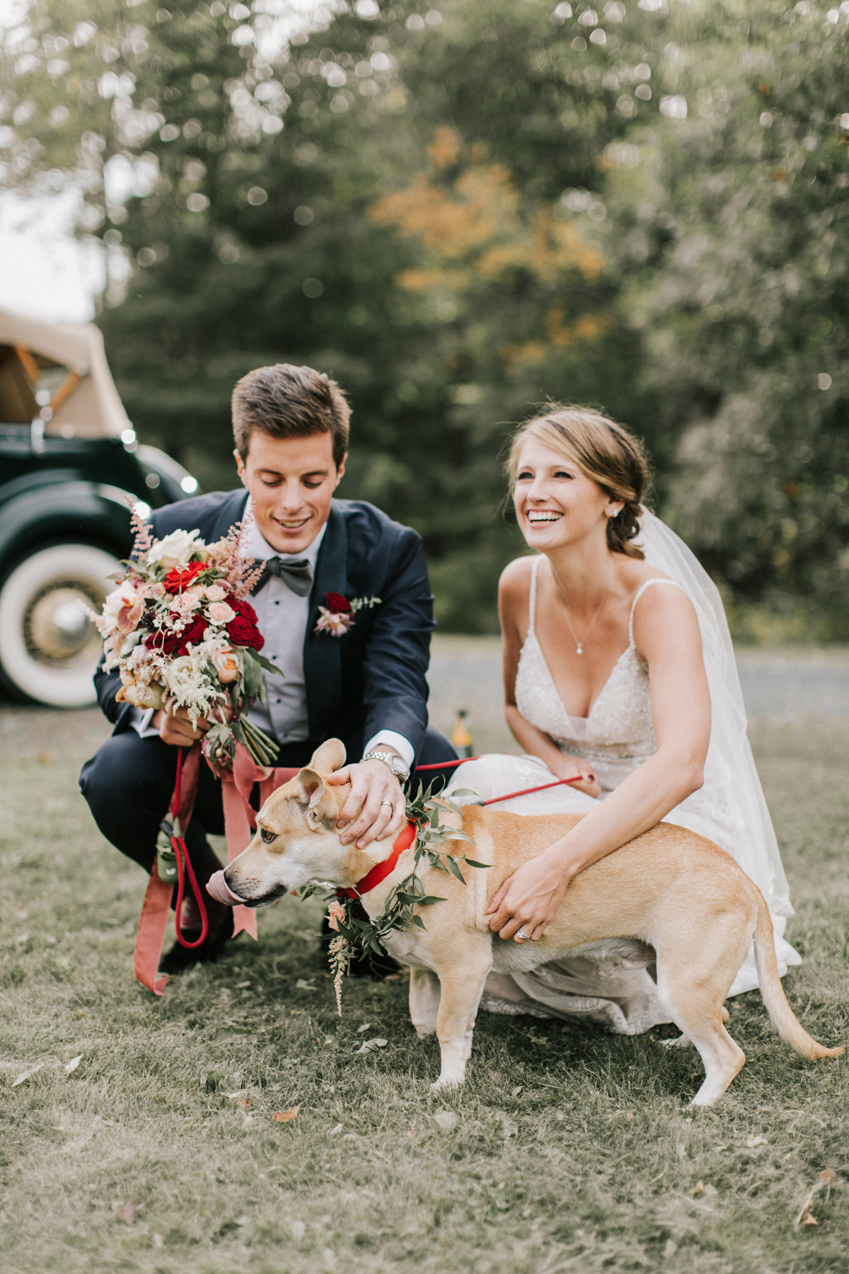 bride and groom take photos with their dog