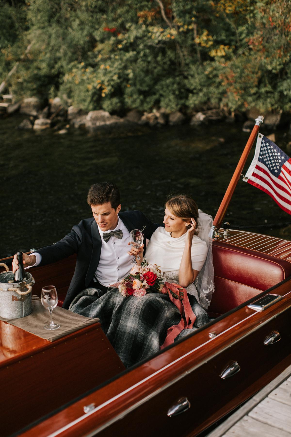 bride and groom sitting in vintage wooden Chris Craft boat