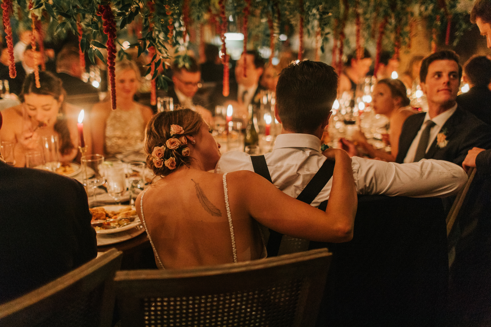 bride and groom sit at reception table with family and friends