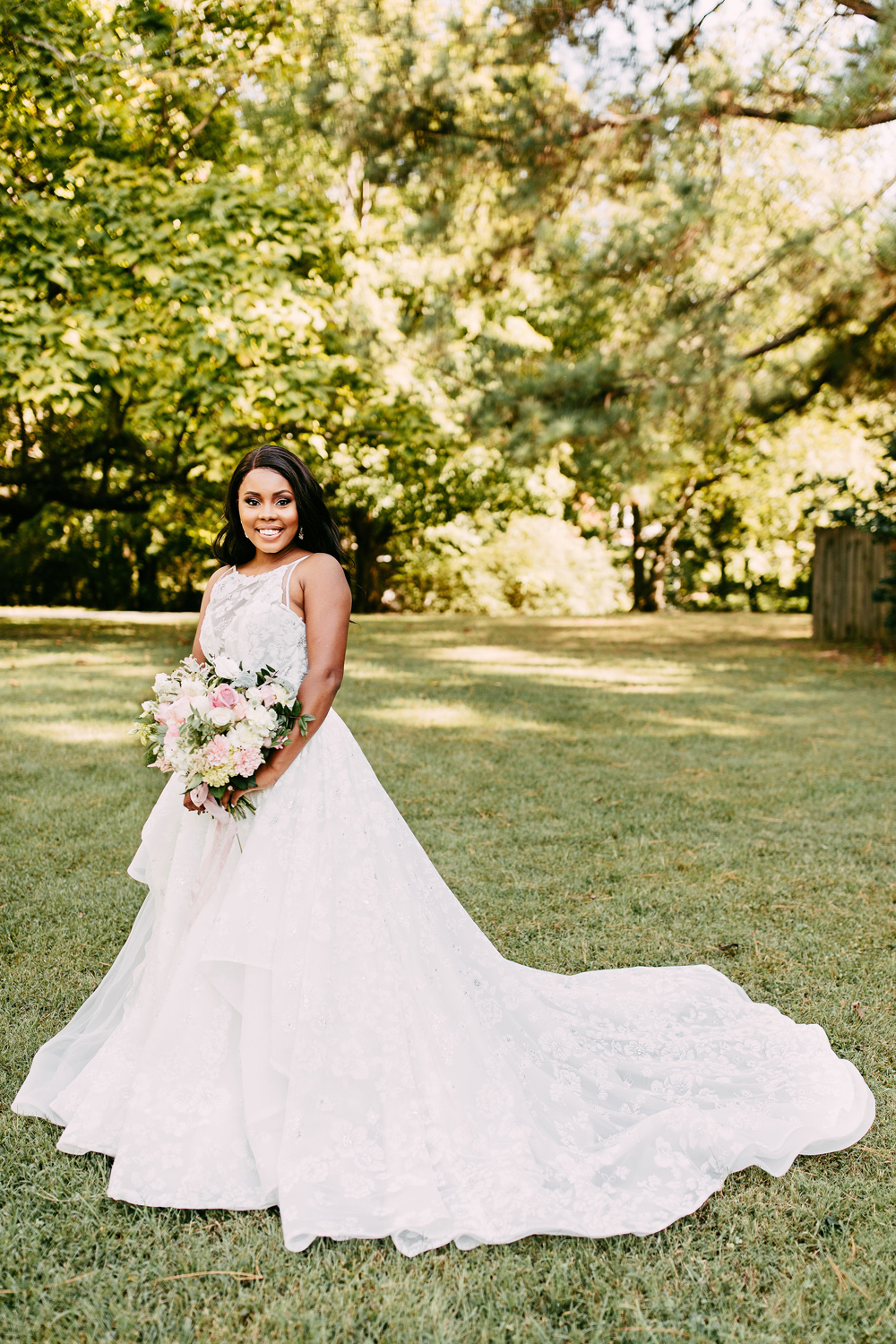 bride posing on lawn wearing princess-style gown