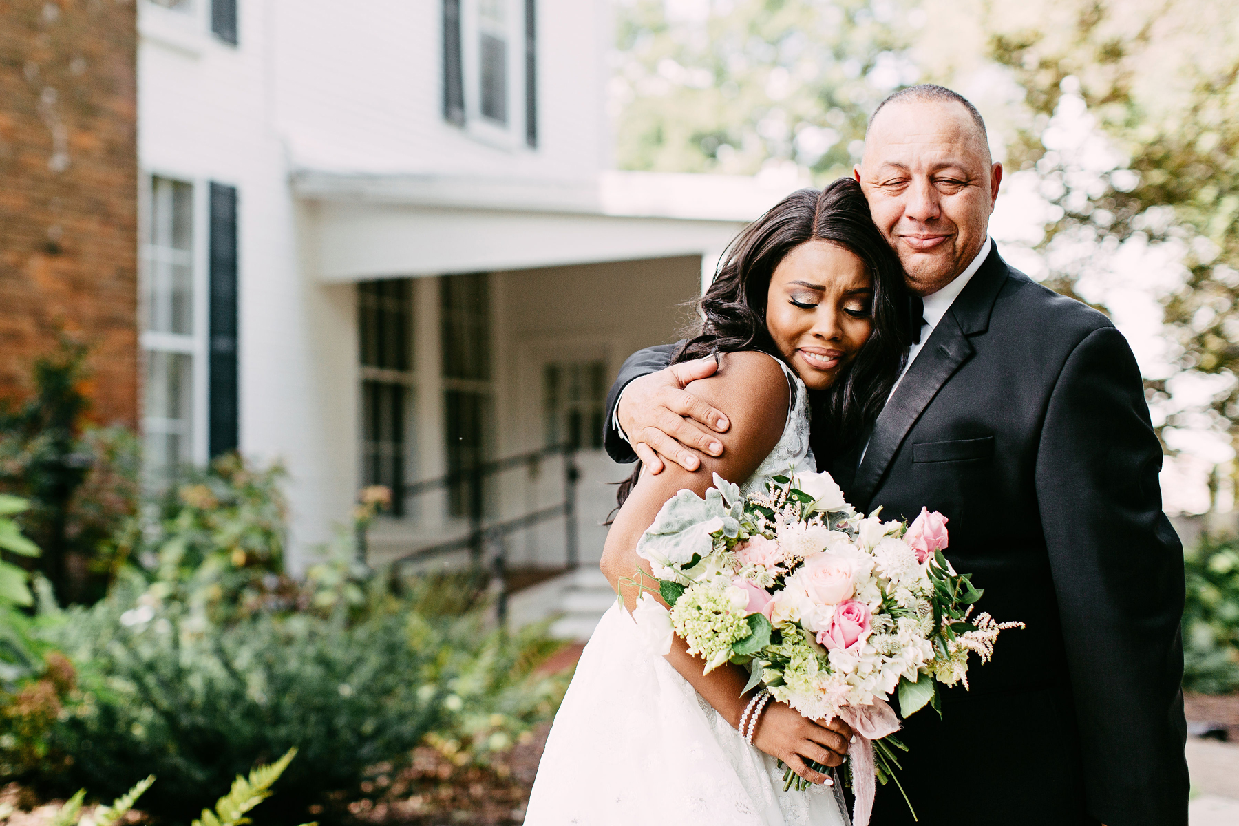 bride and father of the bride embracing