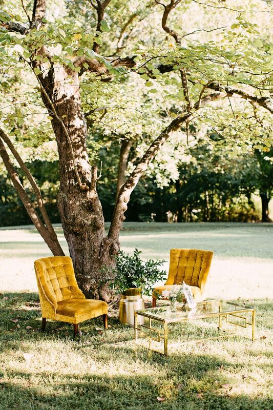 mustard yellow velvet lounge chairs beneath tree