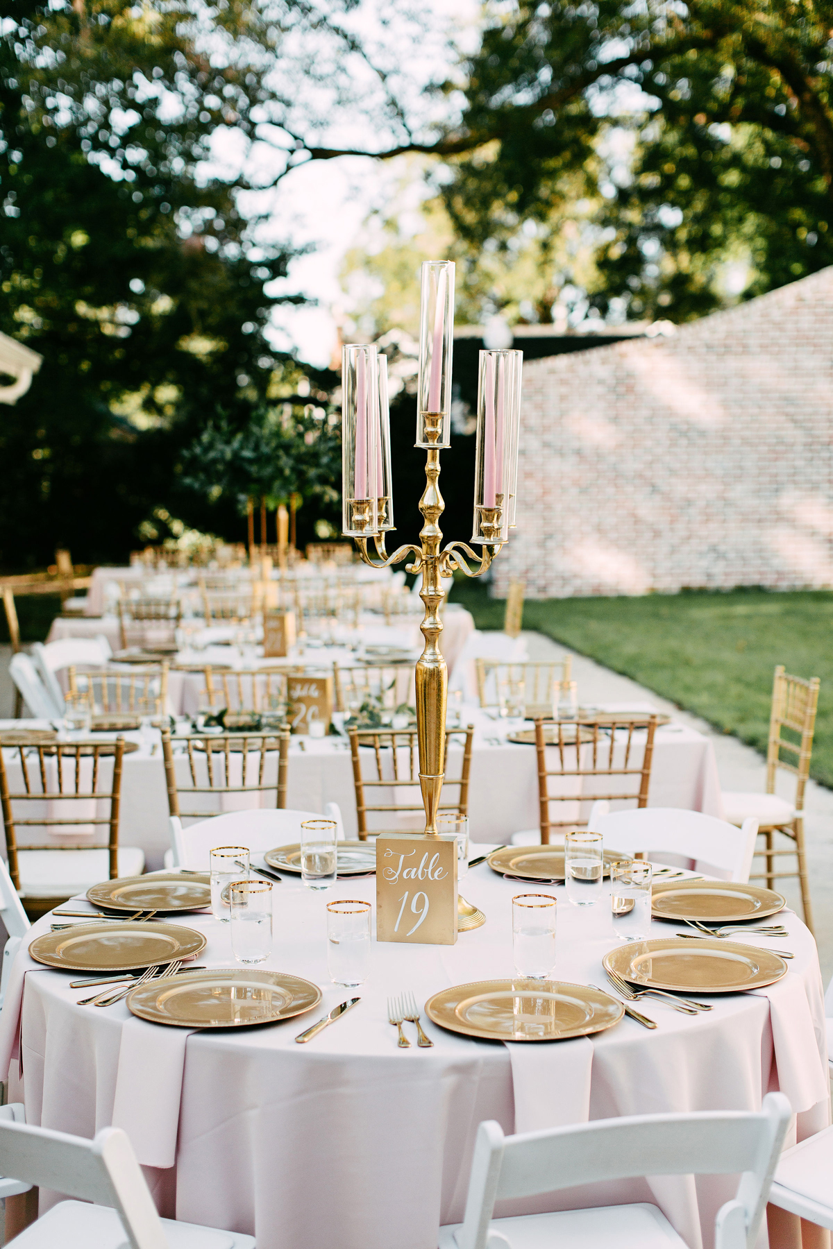round wedding reception tables with gold place settings and pink candles