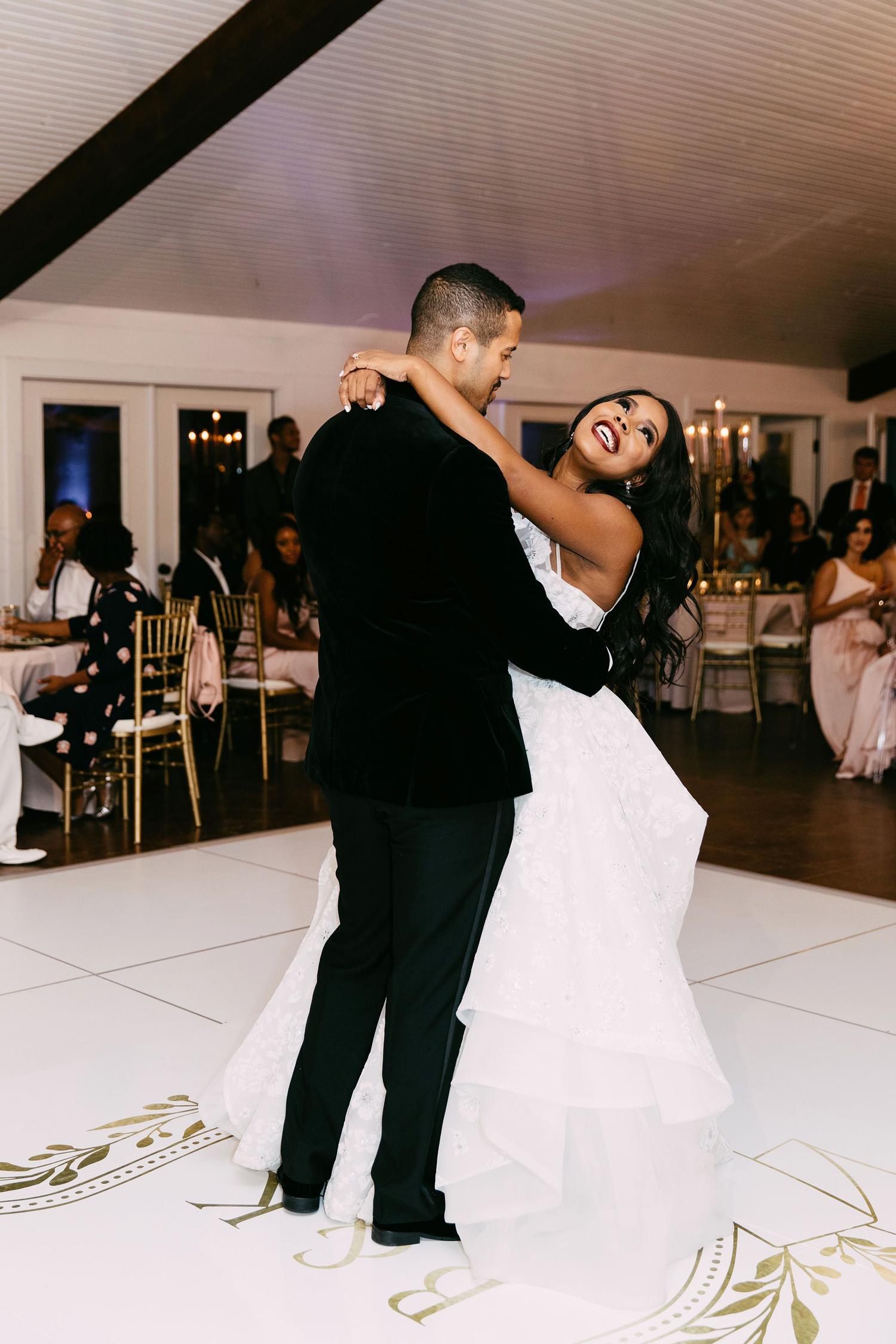 bride and groom sharing first dance on monogrammed dance floor
