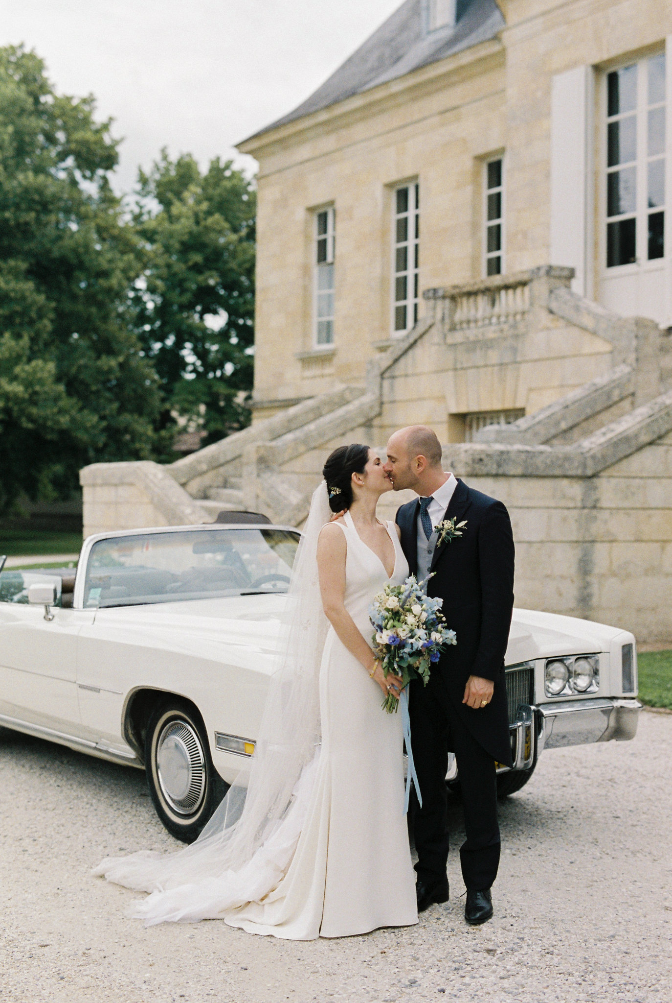bride and groom kiss in front of white vintage convertible car