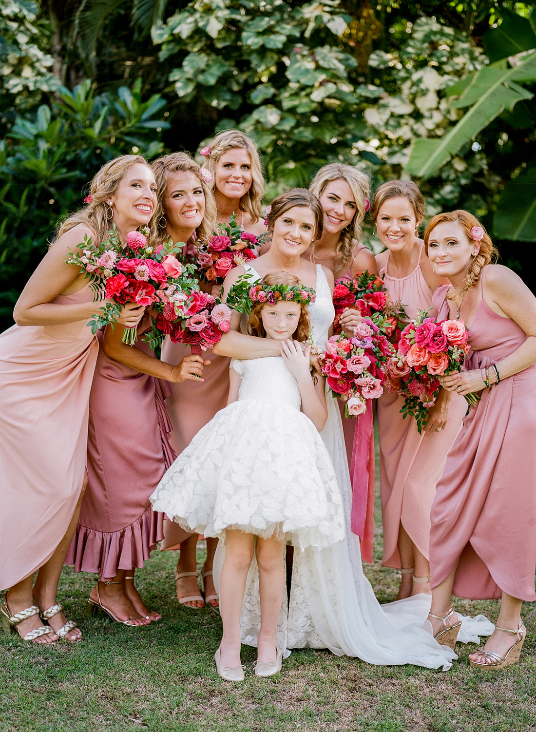 bride with bridesmaids wearing various styles of different dusty rose colored dresses