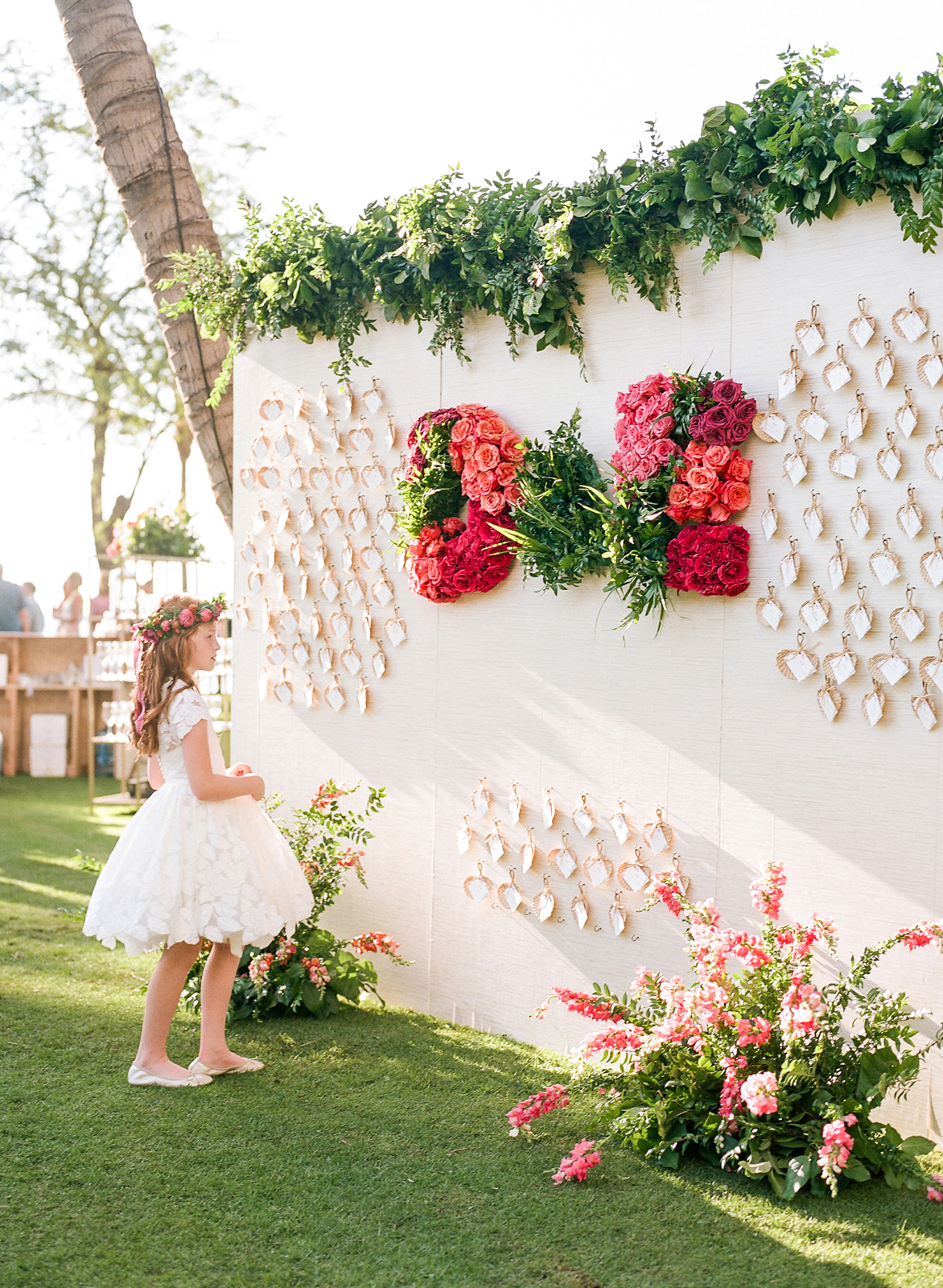 white wall display with seating cards and floral decor