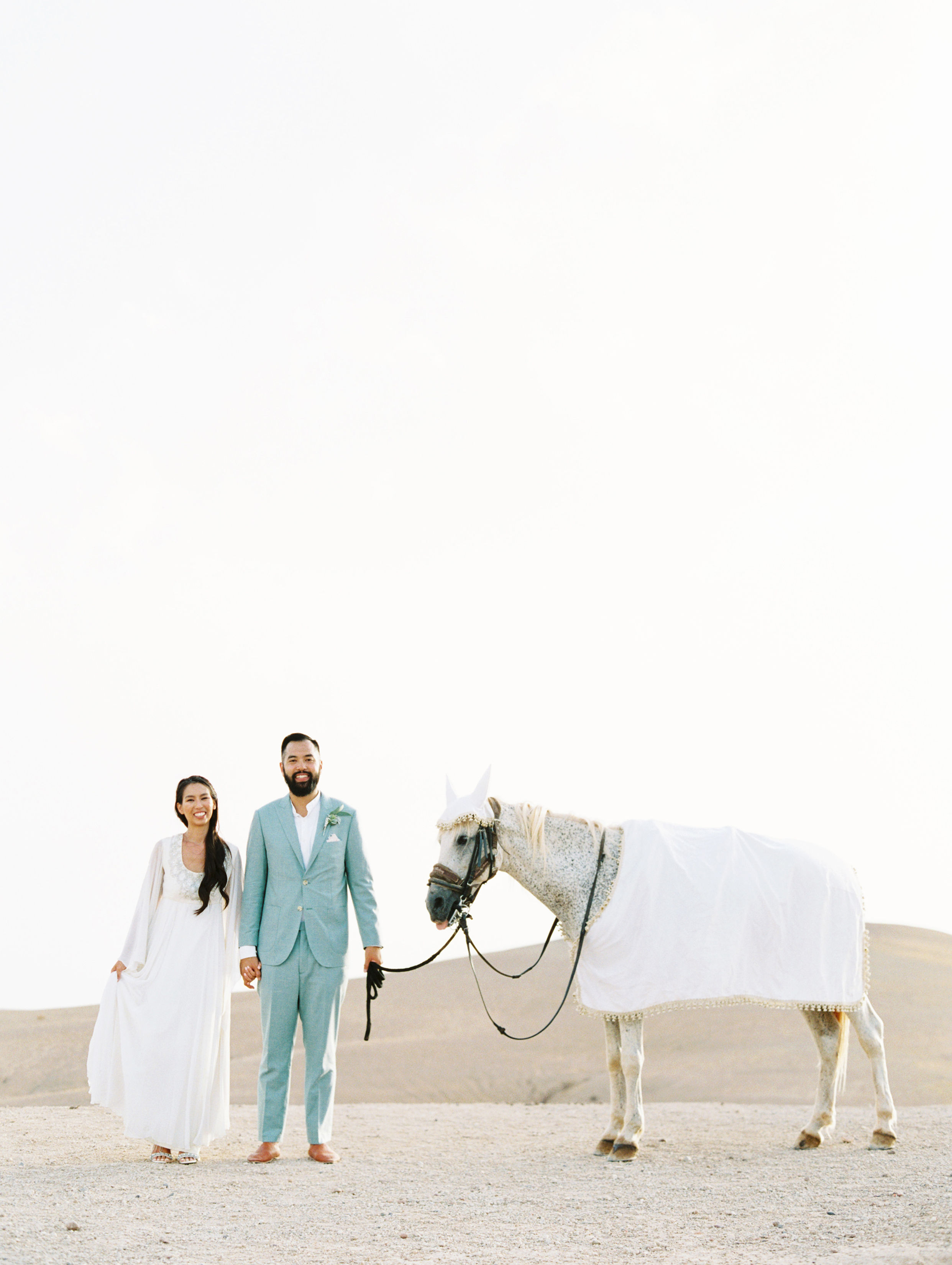 bride and groom stand with horse draped in white linens in the desert