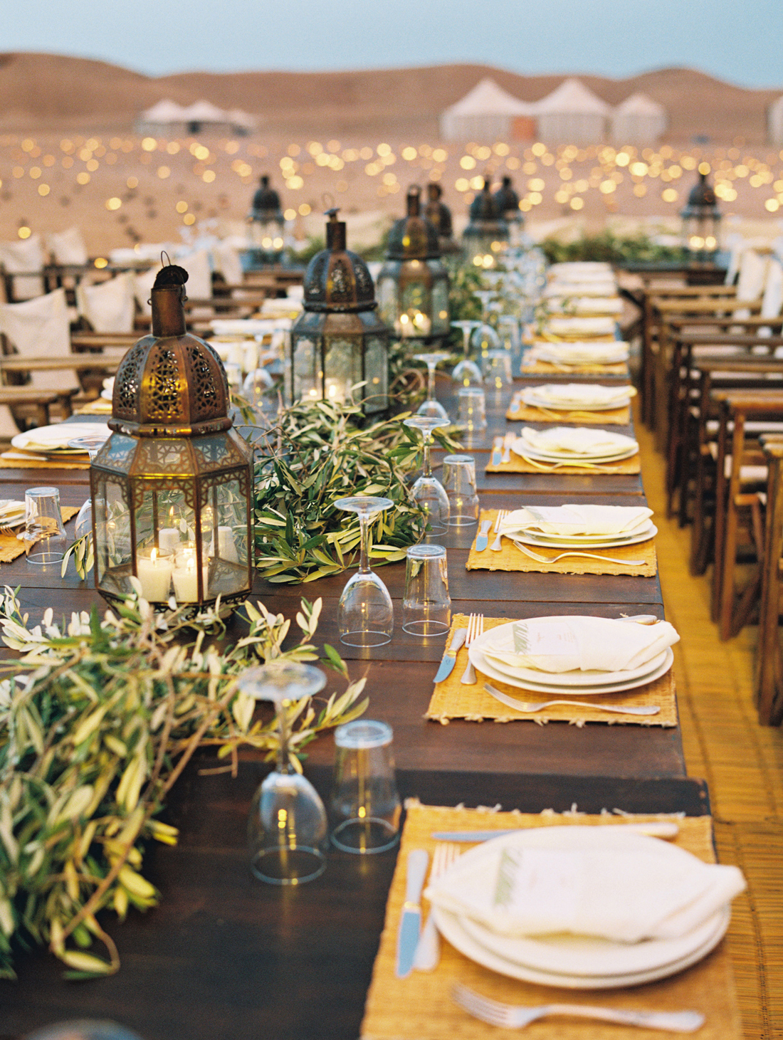 moroccan lantern and greenery centerpieces with woven place mats and white place settings